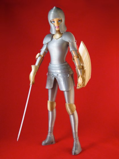 Barbie stands in her silver suit of armor, complete with shield and sword.