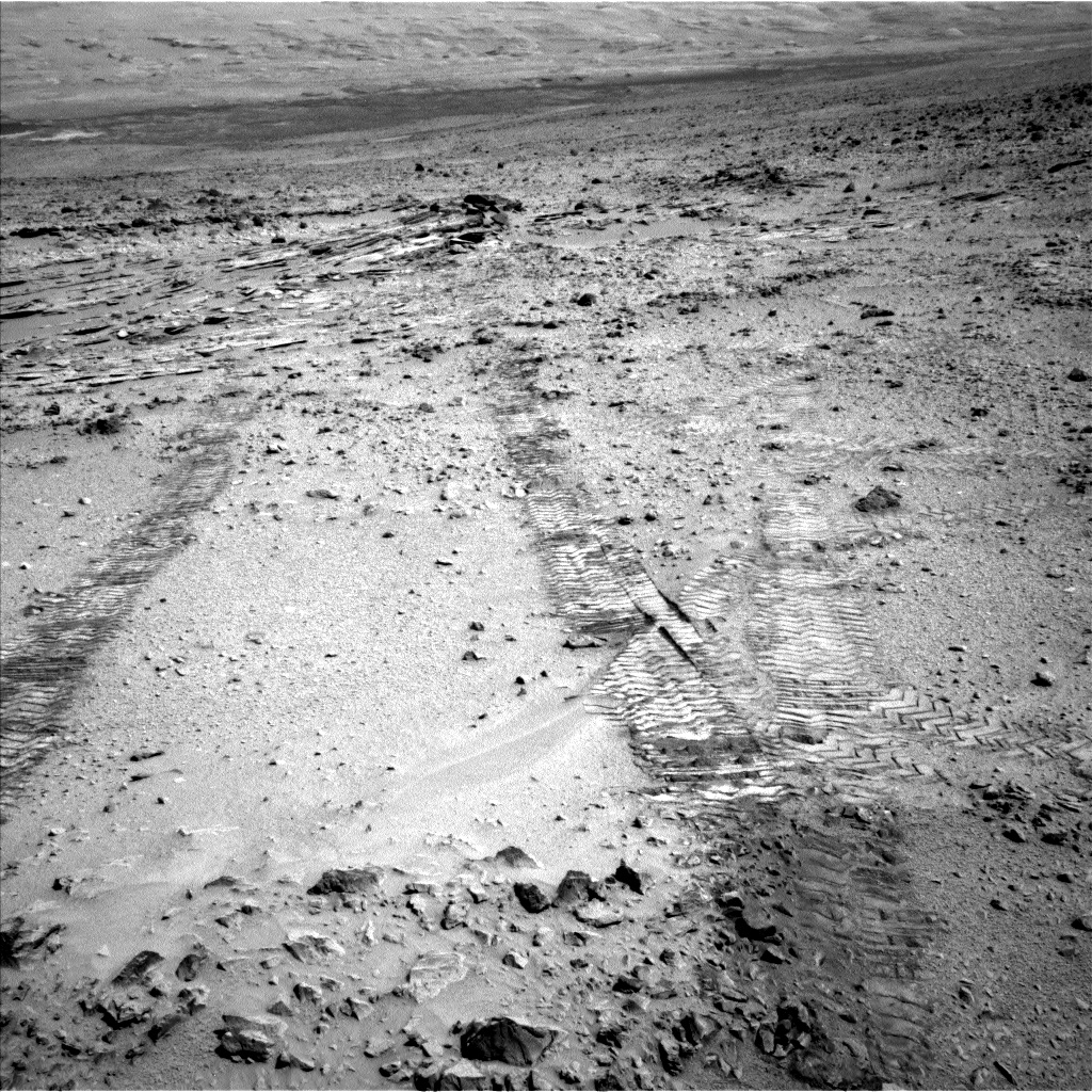 This view from the left Navigation Camera (Navcam) of NASA's Mars Rover Curiosity looks back at wheel tracks made during the first drive away from the last science target in the  Glenelg  area. The drive commenced a long trek toward the mission's long-term destination: Mount Sharp.
