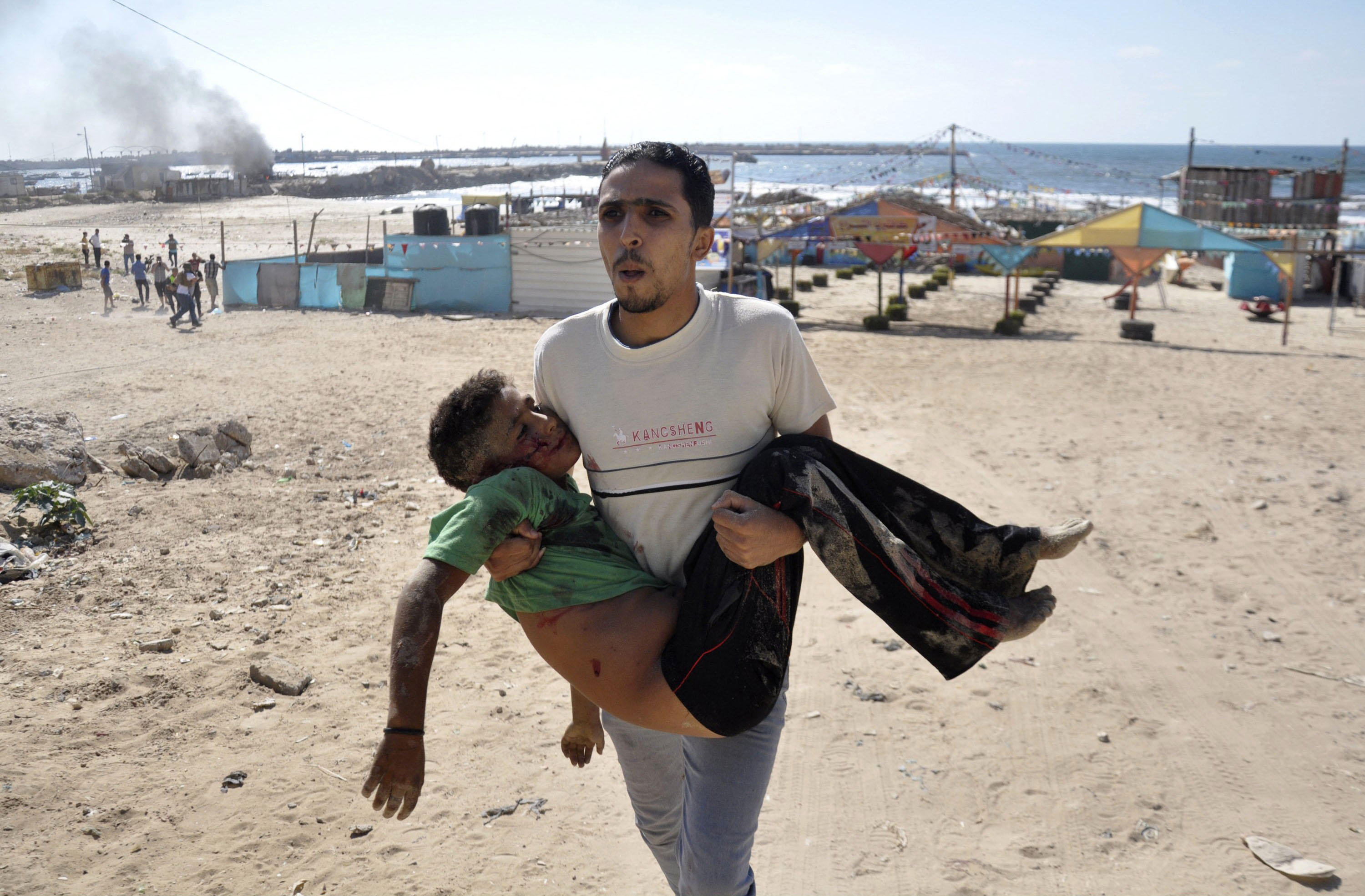 A Palestinian man carries the body of a boy, one of four whom medics say were killed by a shell fired by an Israeli naval gunboat, on a beach in Gaza City.