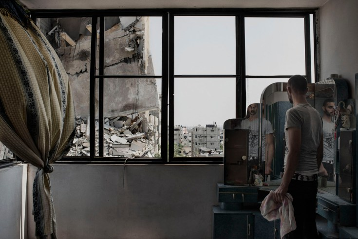 A Palestinian man looks through the window of his house to buildings damaged by an overnight airstrike in Gaza City, July 22, 2014.