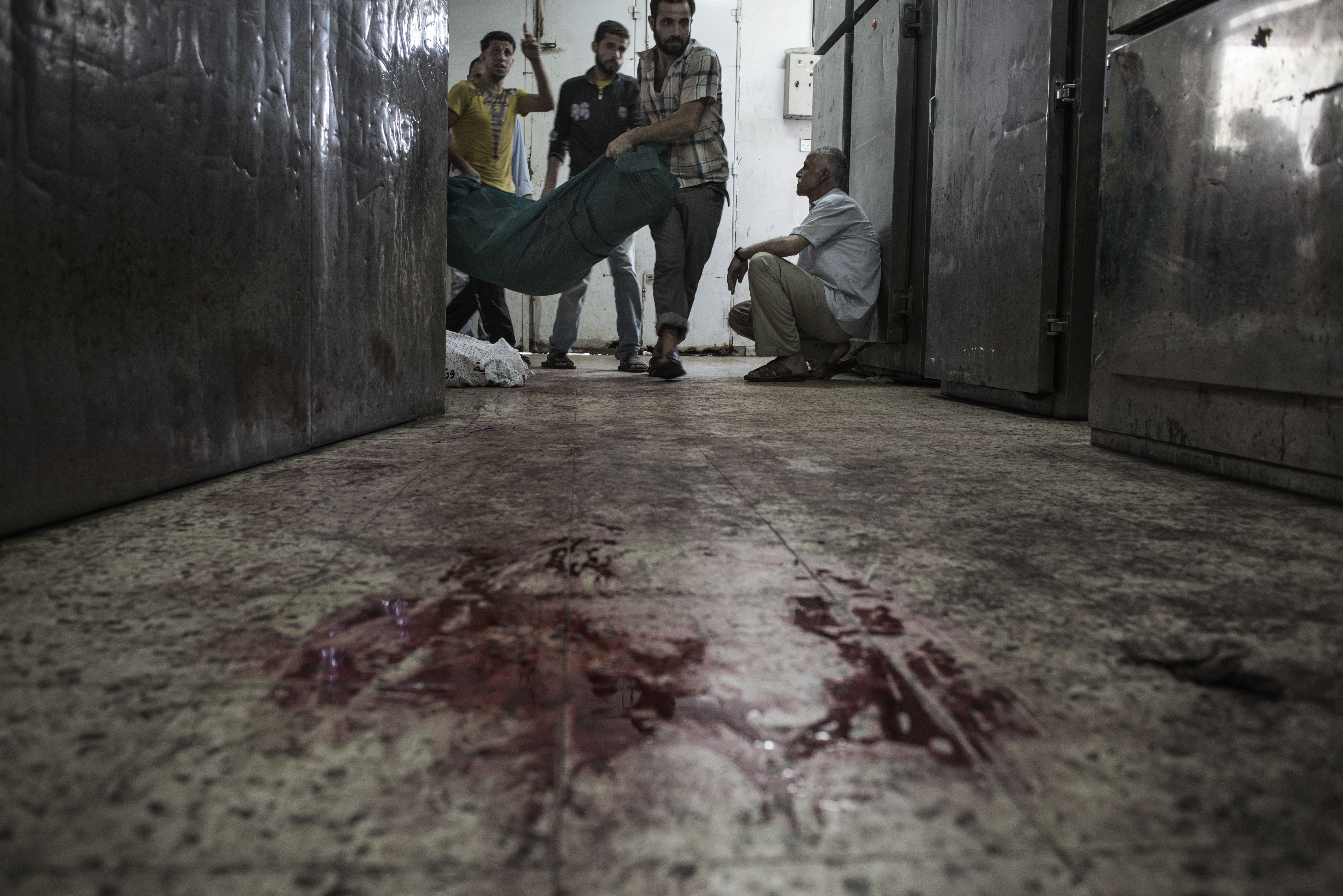 Palestinians carry a body into the Shifa Hospital morgue, Gaza City, July 20, 2014.