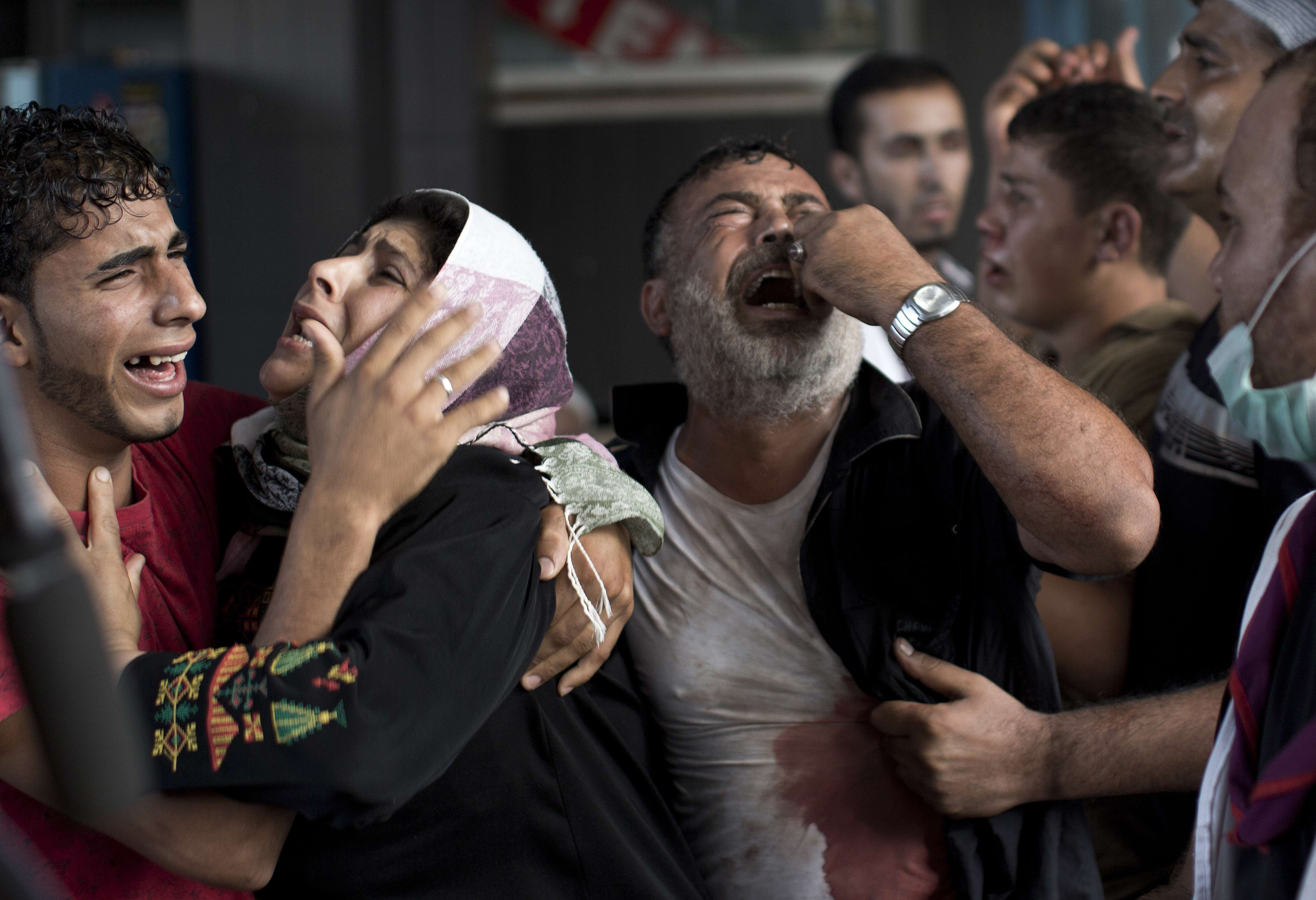 Palestinian mourners cry at al-Shifa Hospital in Gaza City after an explosion killed at least seven children in a public playground in the beachfront Shati refugee camp on July 28, 2014