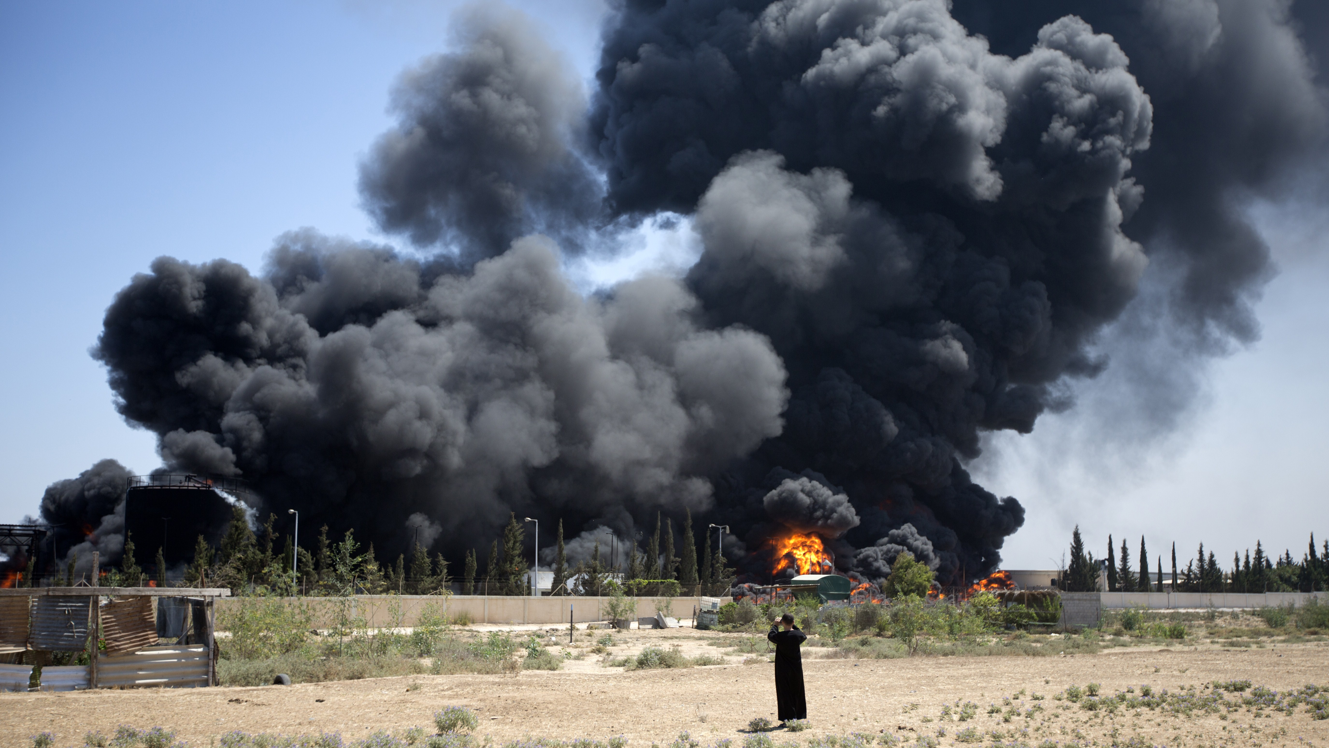 A Palestinian man stands looking as flames engulf the fuel tanks of the only power plant supplying electricity to the Gaza Strip after it was hit by overnight Israeli shelling, on July 29, 2014, in the south of Gaza City.