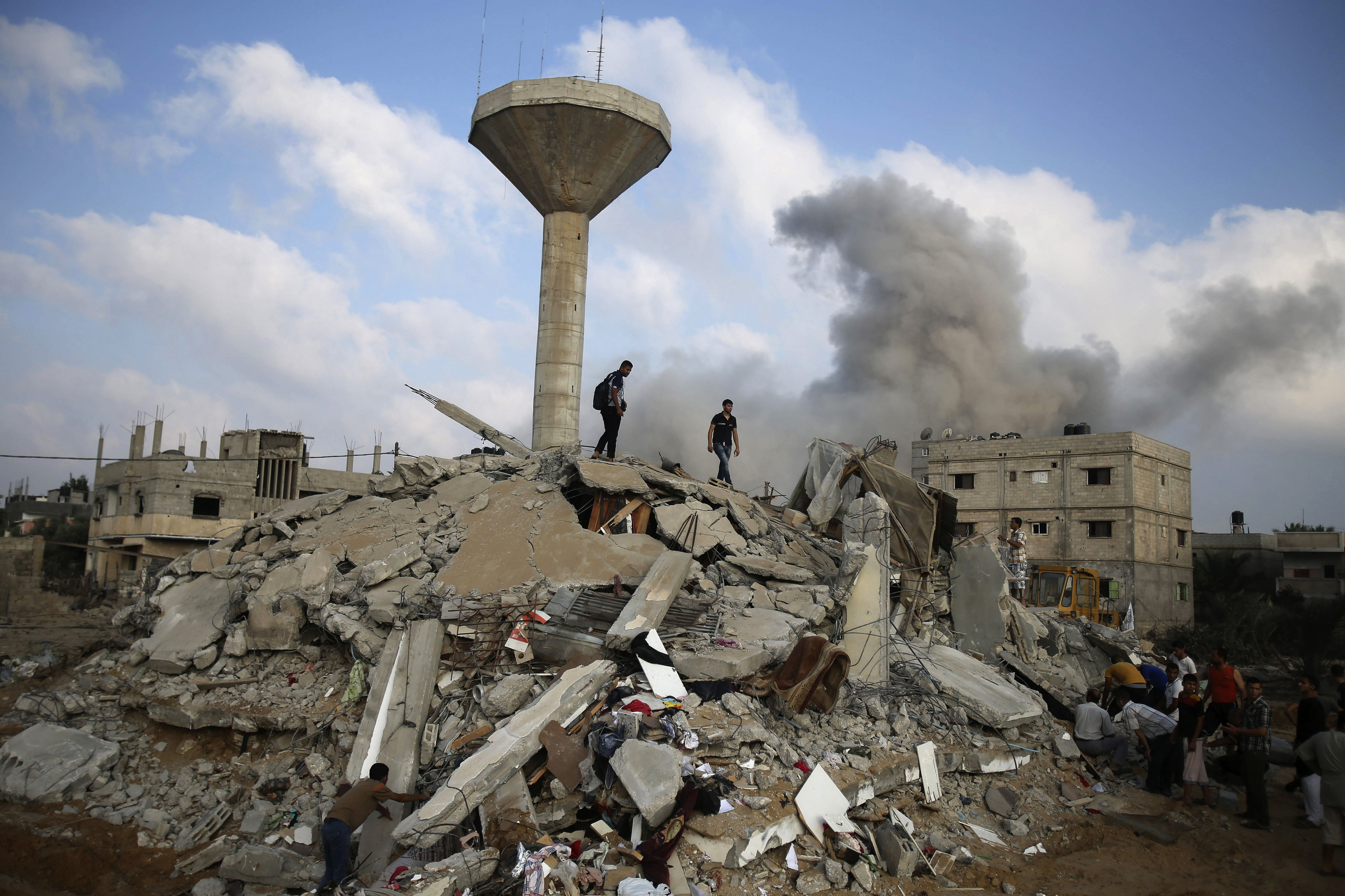 Palestinians search for victims as people gather atop the remains of a house, which witnesses said was destroyed in an Israeli air strike, in Rafah in the southern Gaza Strip on July 29, 2014.