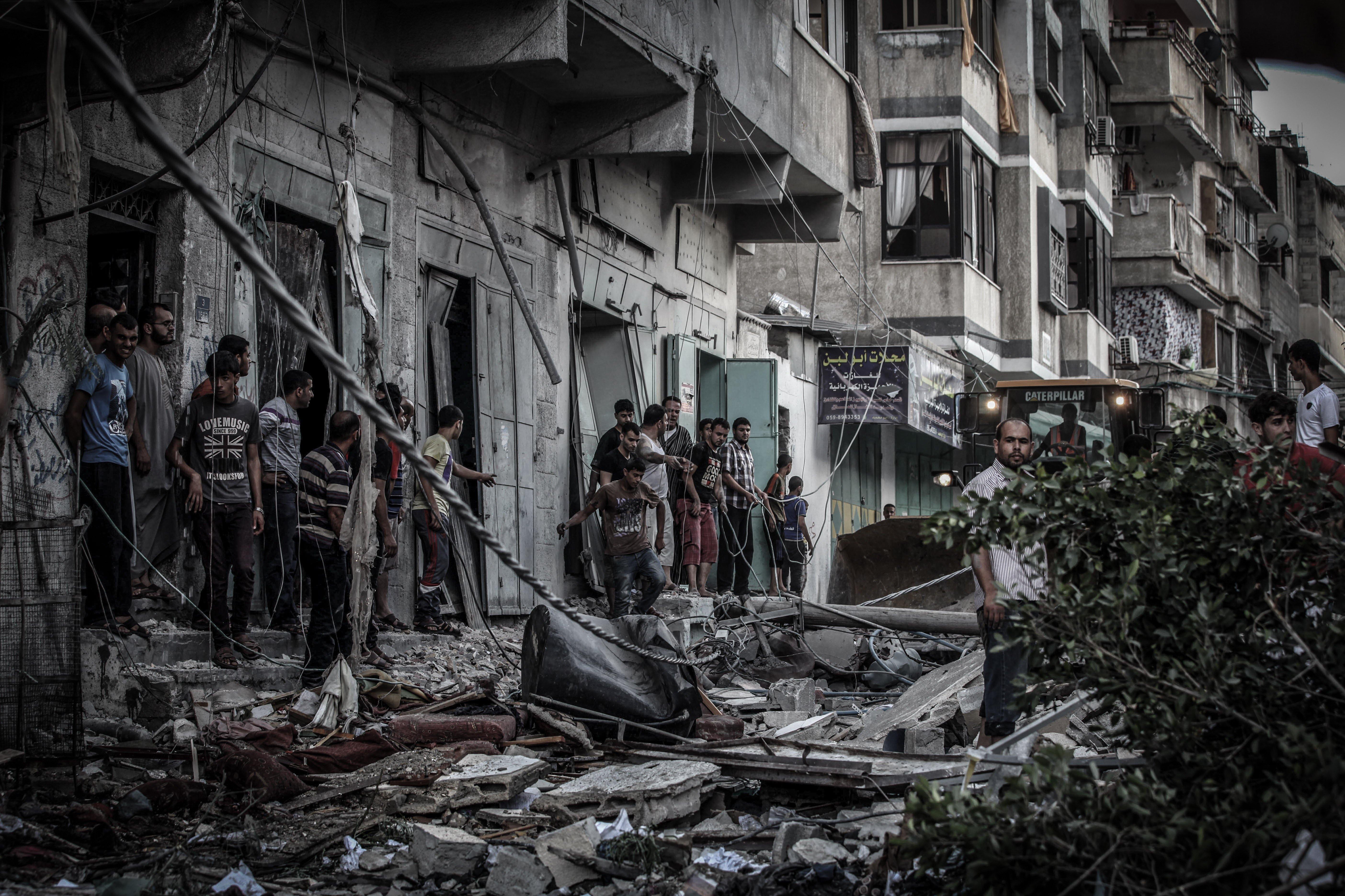 Palestinians inspect damage of an apartment building after it was hit by an Israeli missile strike in Gaza City, Friday, July 18, 2014.