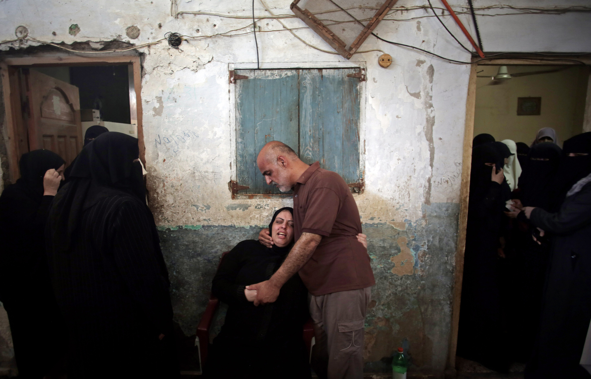 Palestinian relatives of eight members of the Al Haj family, who were killed in a strike early morning, grieve in the family house during their funeral in Khan Younis refugee camp, southern Gaza Strip, July 10, 2014.
