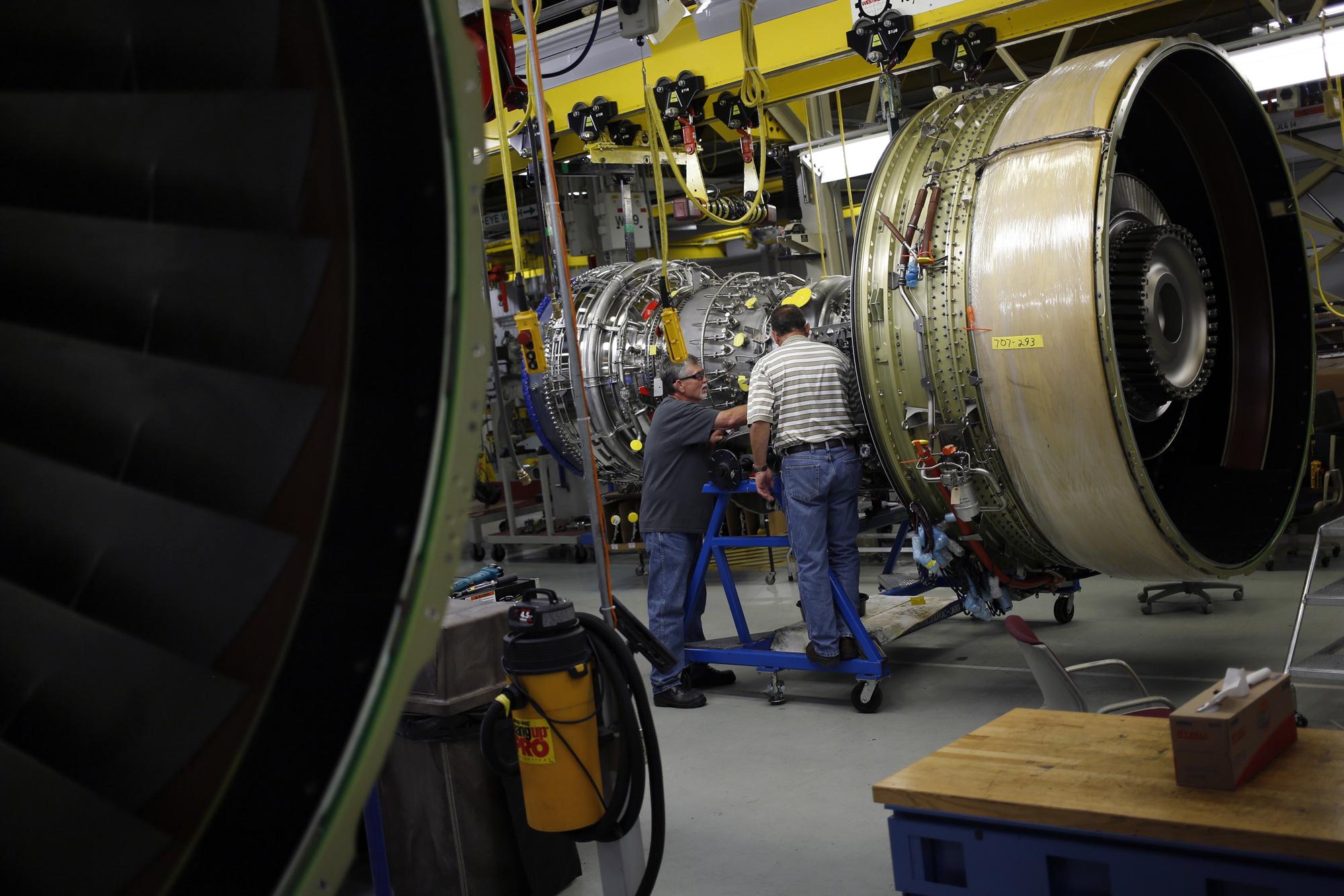 Workers assemble a General Electric Co. CF6-80C2 jet engine at the GE Aviation factory in Cincinnati, Ohio, June 25, 2014.