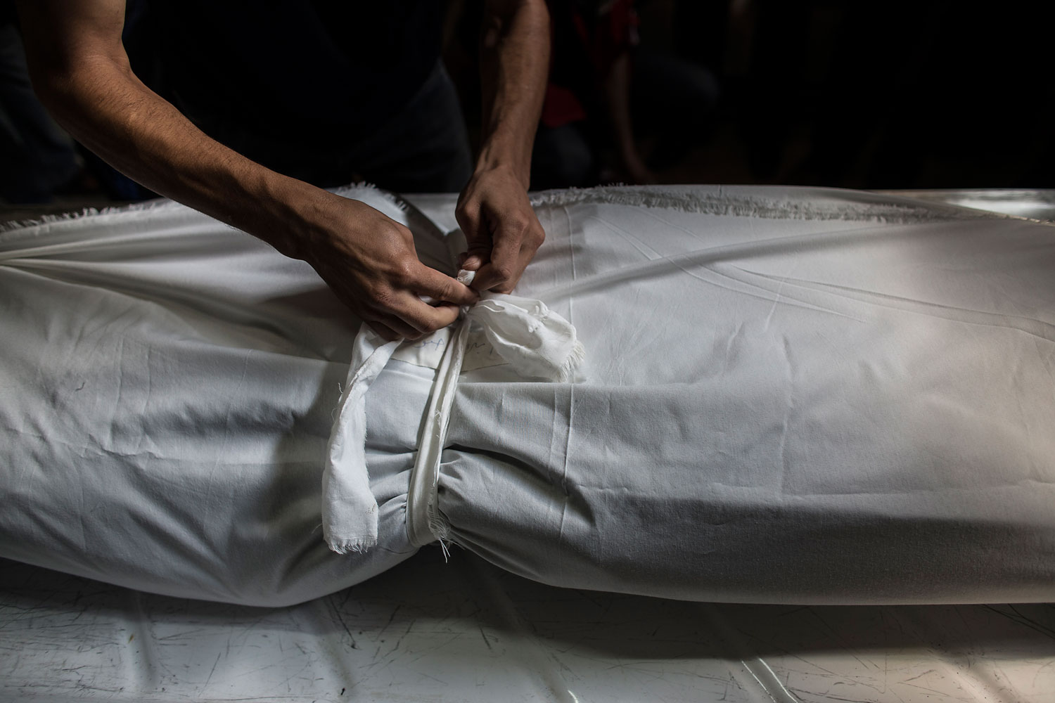 A Palestinian mortician ties a knot around the sheet covering the body of a dead Palestinian man in a morgue in Khan Younis, central Gaza City, July 18, 2014.