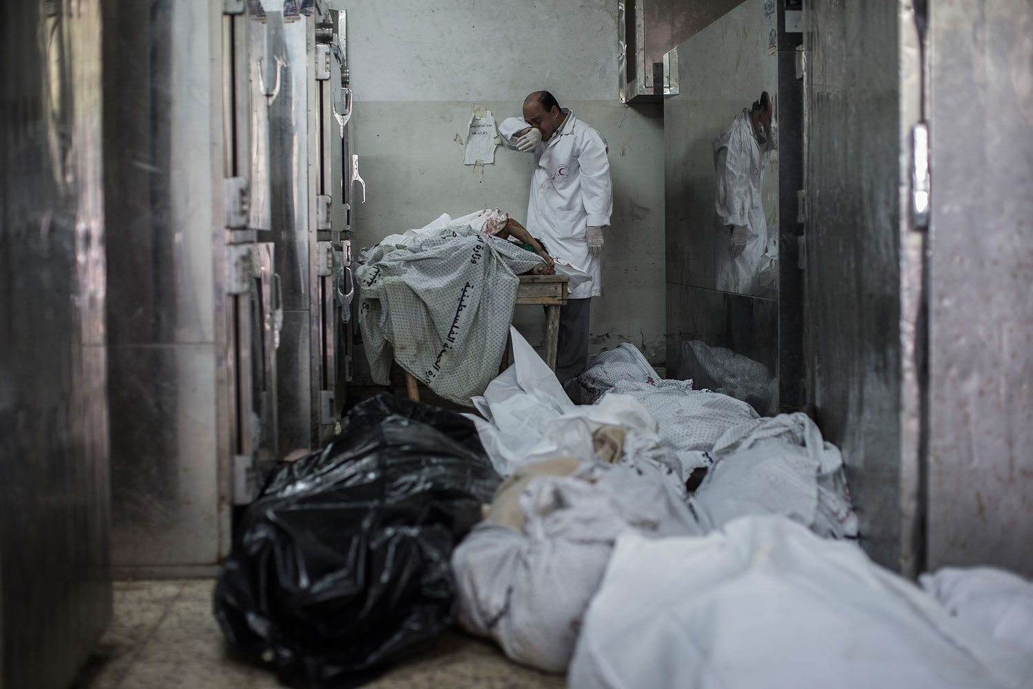 A doctor cries while standing next to a table with the bodies of four dead children in overflowing morgue of the Shifa hospital in Gaza City, July 20, 2014.