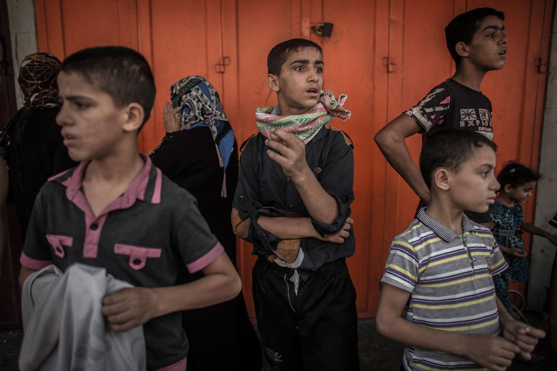 Palestinians boys watch people fleeing from Shuja'iyya neighbourhood in east Gaza City, 20 July 2014.