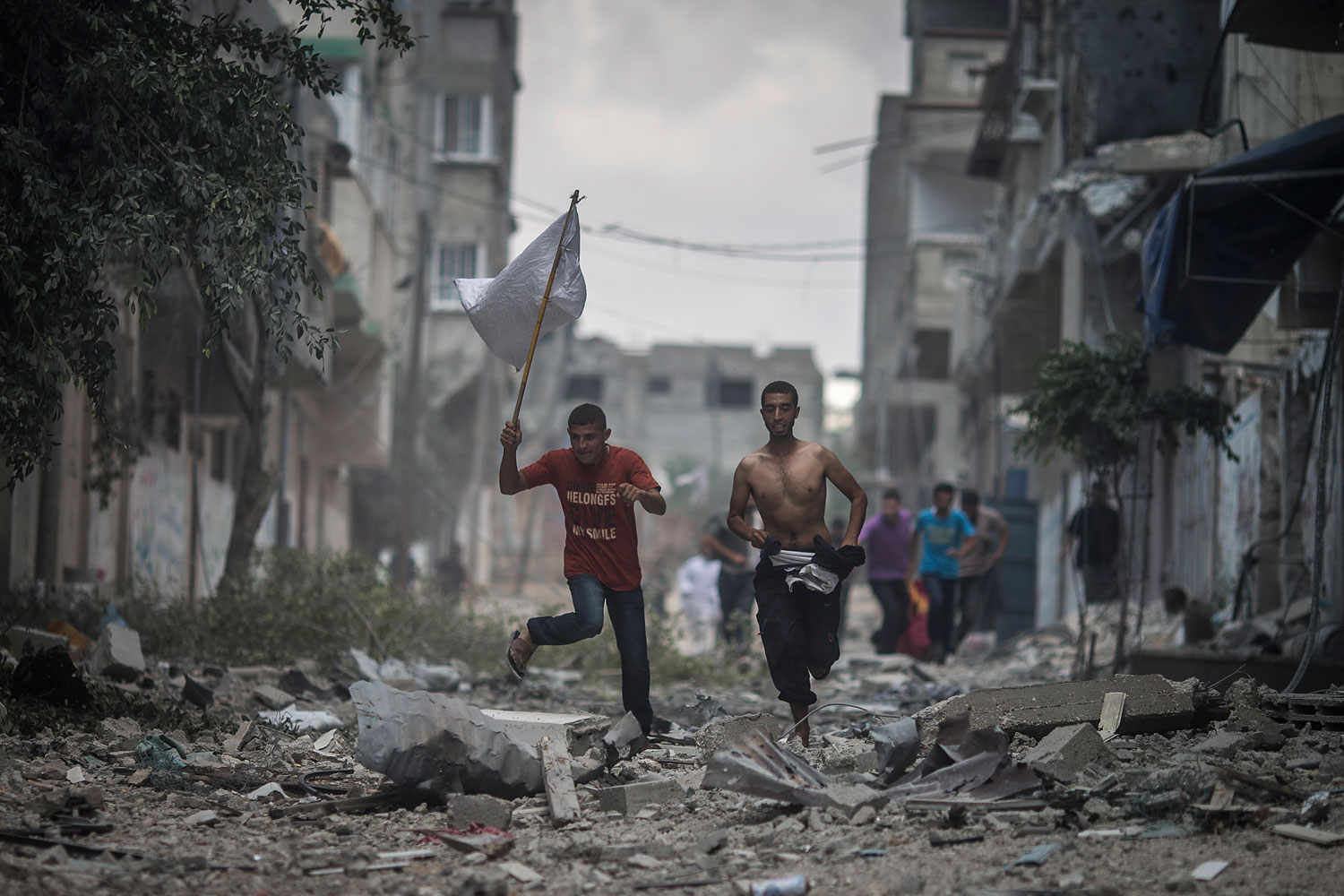 Two Palestinian men carry a white flag as they flee their homes during a brief period of ceasefire requested by local rescue forces to retrieve dead and wounded from the Shuja'iyya neighbourhood in east Gaza City, July 20, 2014.