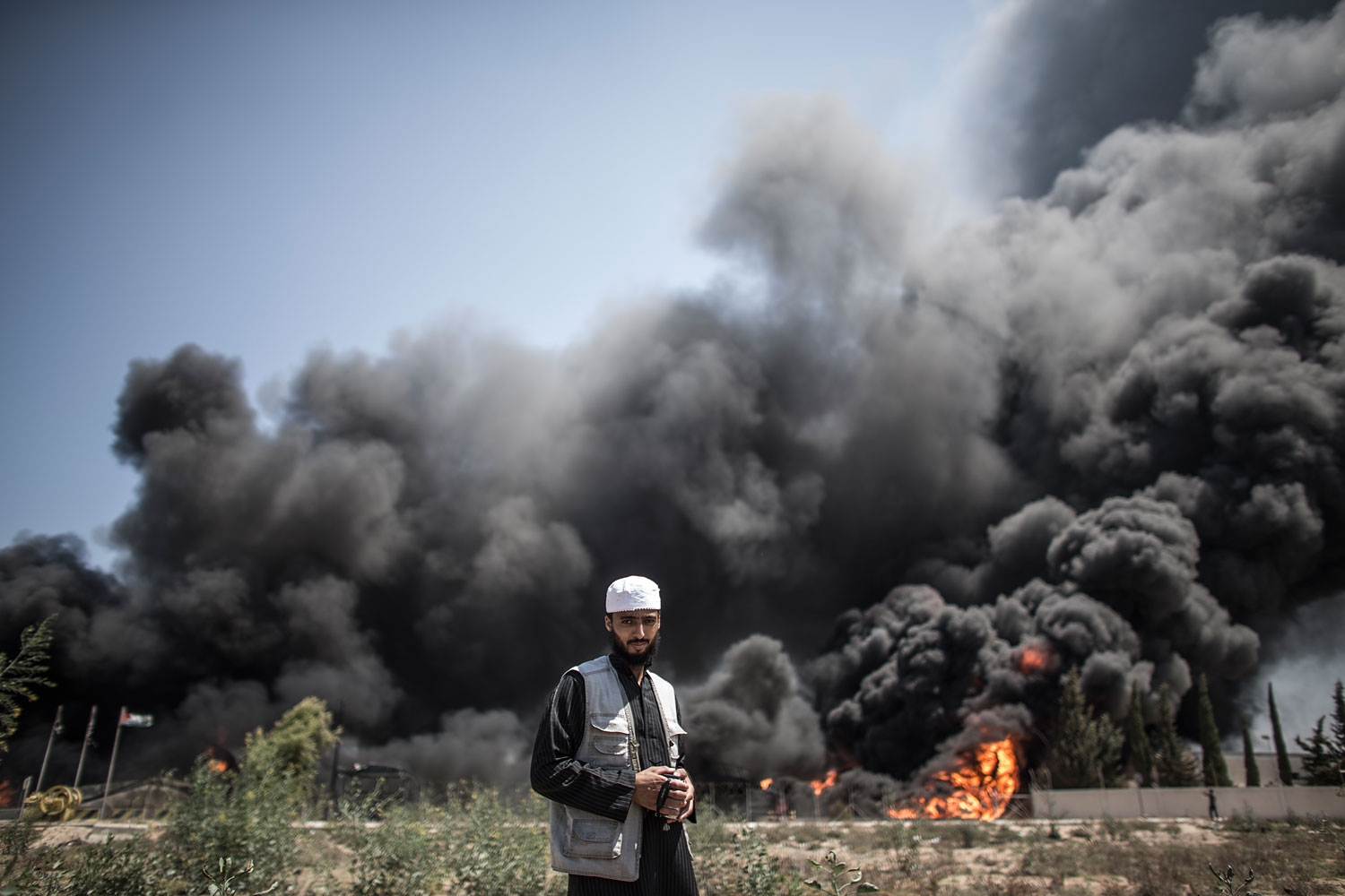 A Palestinian man walks in front of a fire raging at Gaza's main power plant on July 29, 2014, in Gaza City, following an overnight Israeli air strike