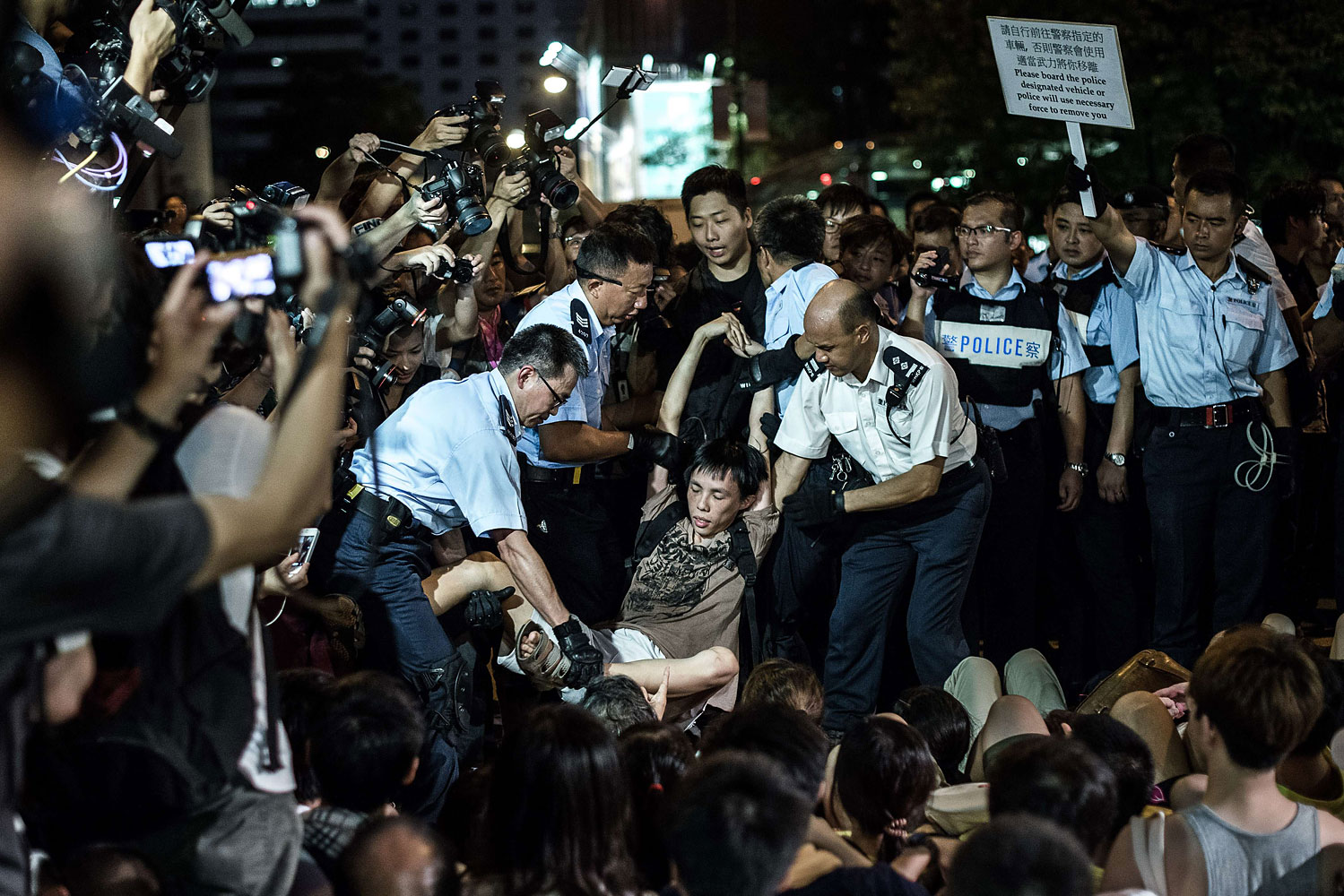 Policemen remove protesters in Central district after a rally seeking greater democracy in Hong Kong on July 2, 2014
