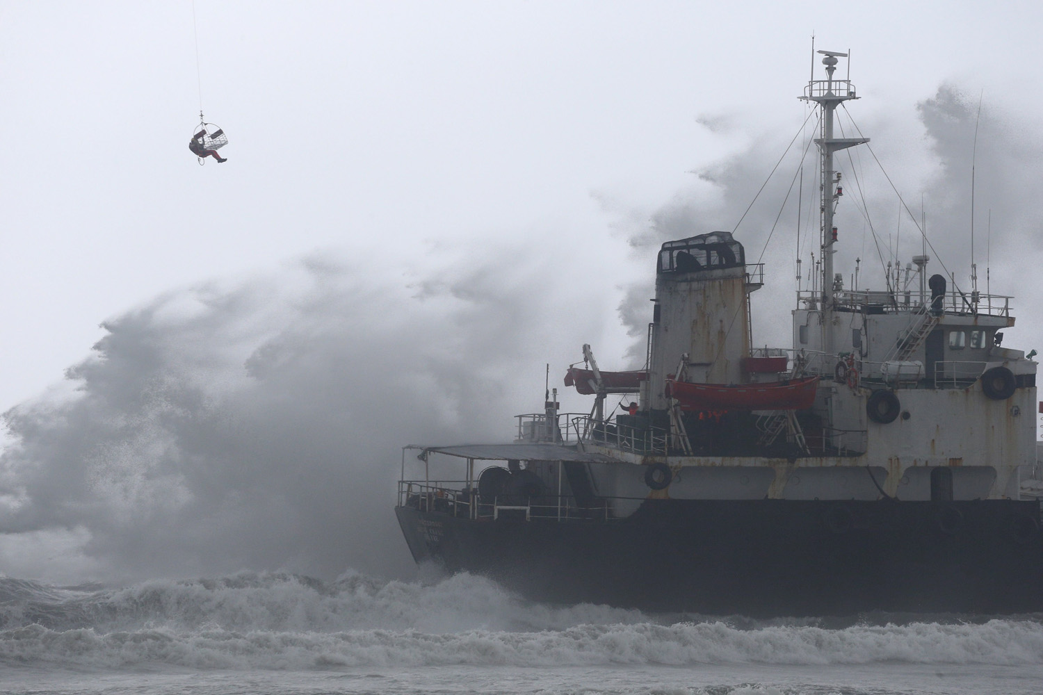 Jul. 23, 2014. A Chinese worker is lifted from a helicopter near the Sheng Chang oil tanker as it runs aground at Kaohsiung harbor as Typhoon Matmo hit.