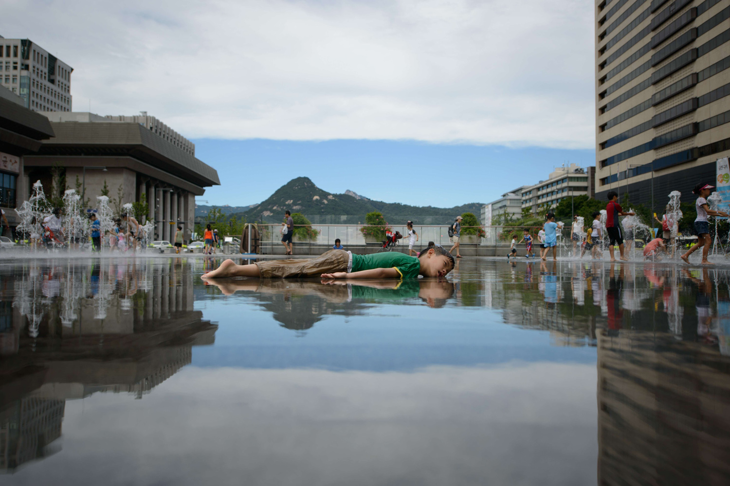 Aug. 1, 2014. A child lies in a pool of water to cool down in central Seoul, South Korea.