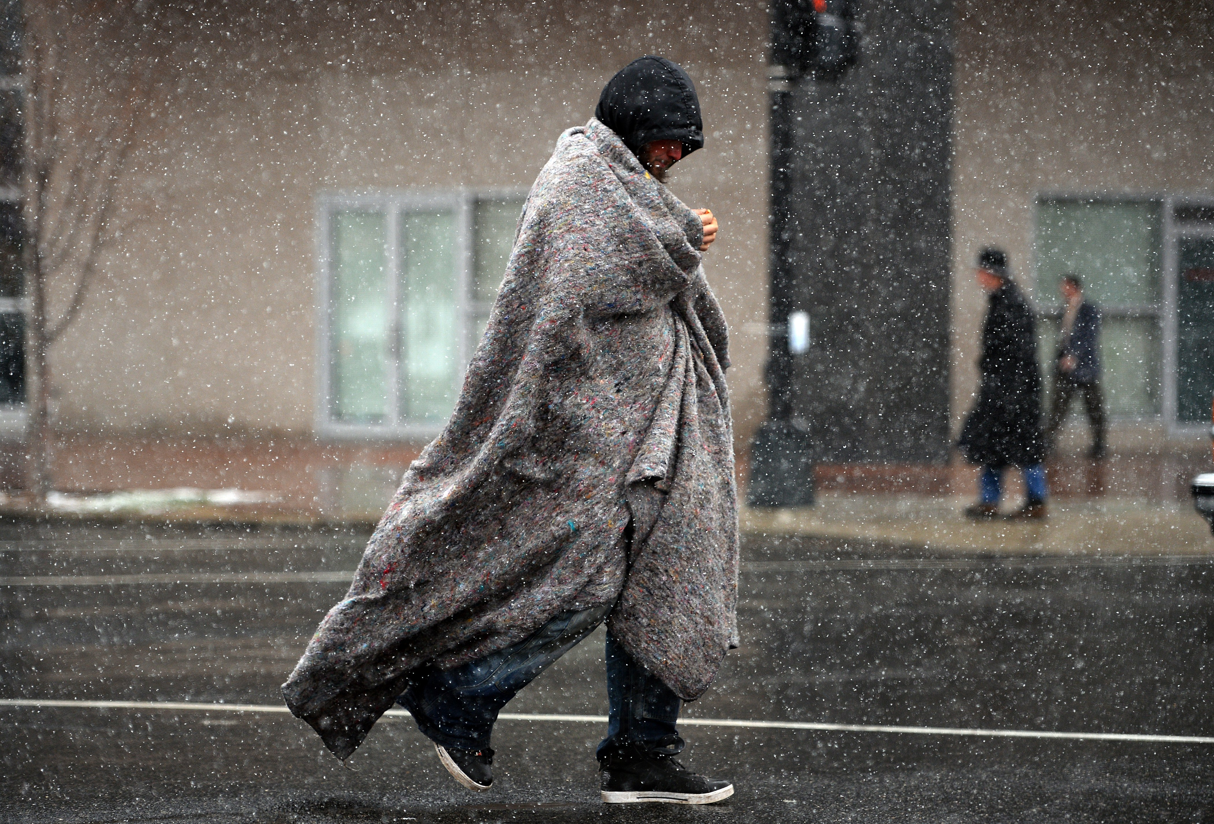 A man covers himself as he crosses a street under a snowfall in Washington, D.C. on March 25, 2014.