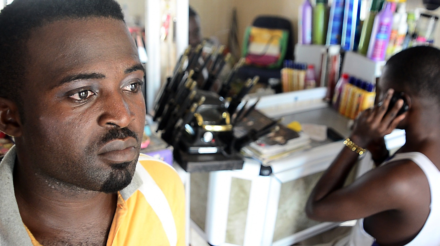 Nana Yaw, a human rights activist an openly gay man, sits with his friend in his sister's hair salon in Accra, Ghana on March 21, 2013.