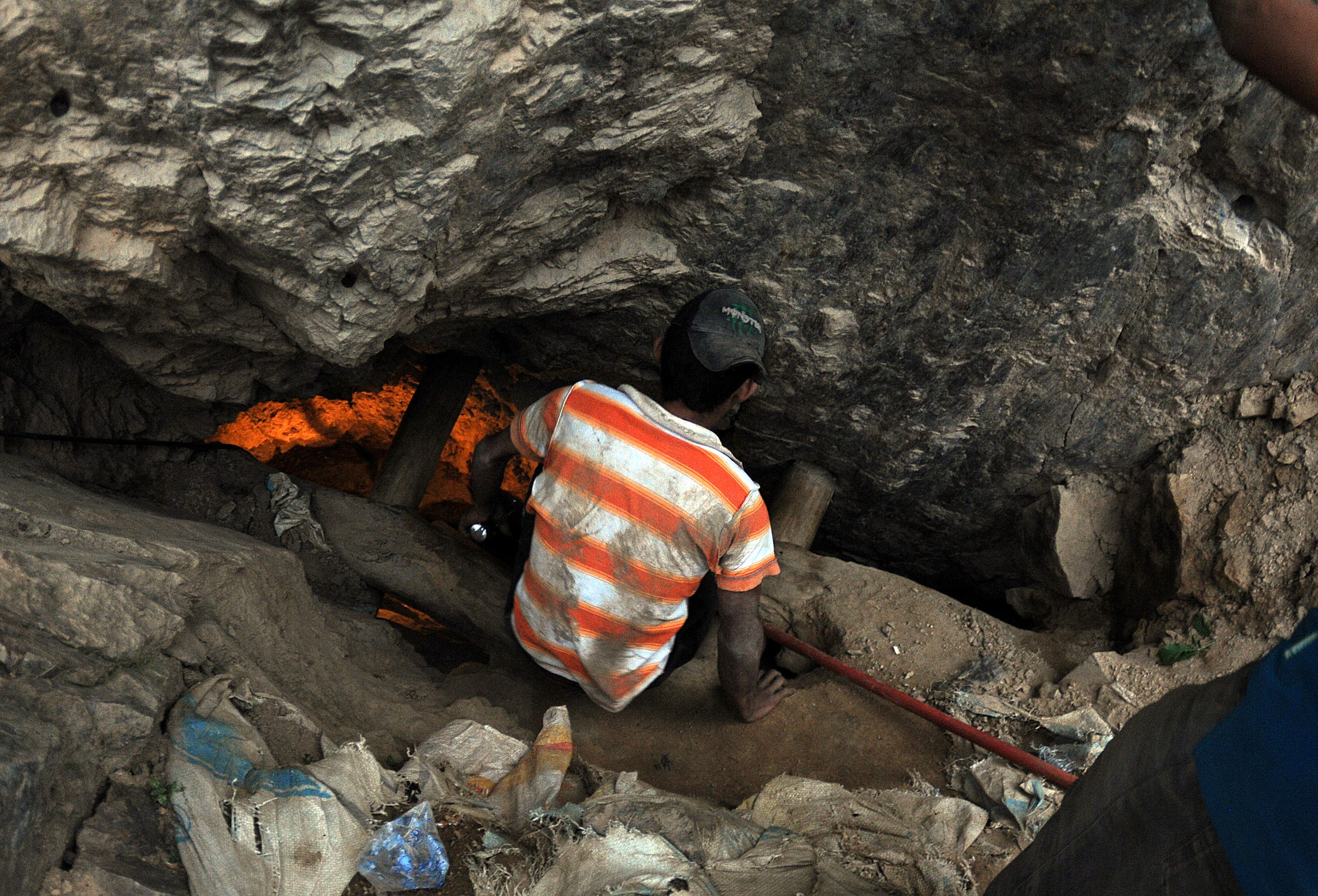 A man looks into a gold mine where miners are trapped after a landslide in San Juan Arriba, Choluteca, in southern Honduras, July 3, 2014.
