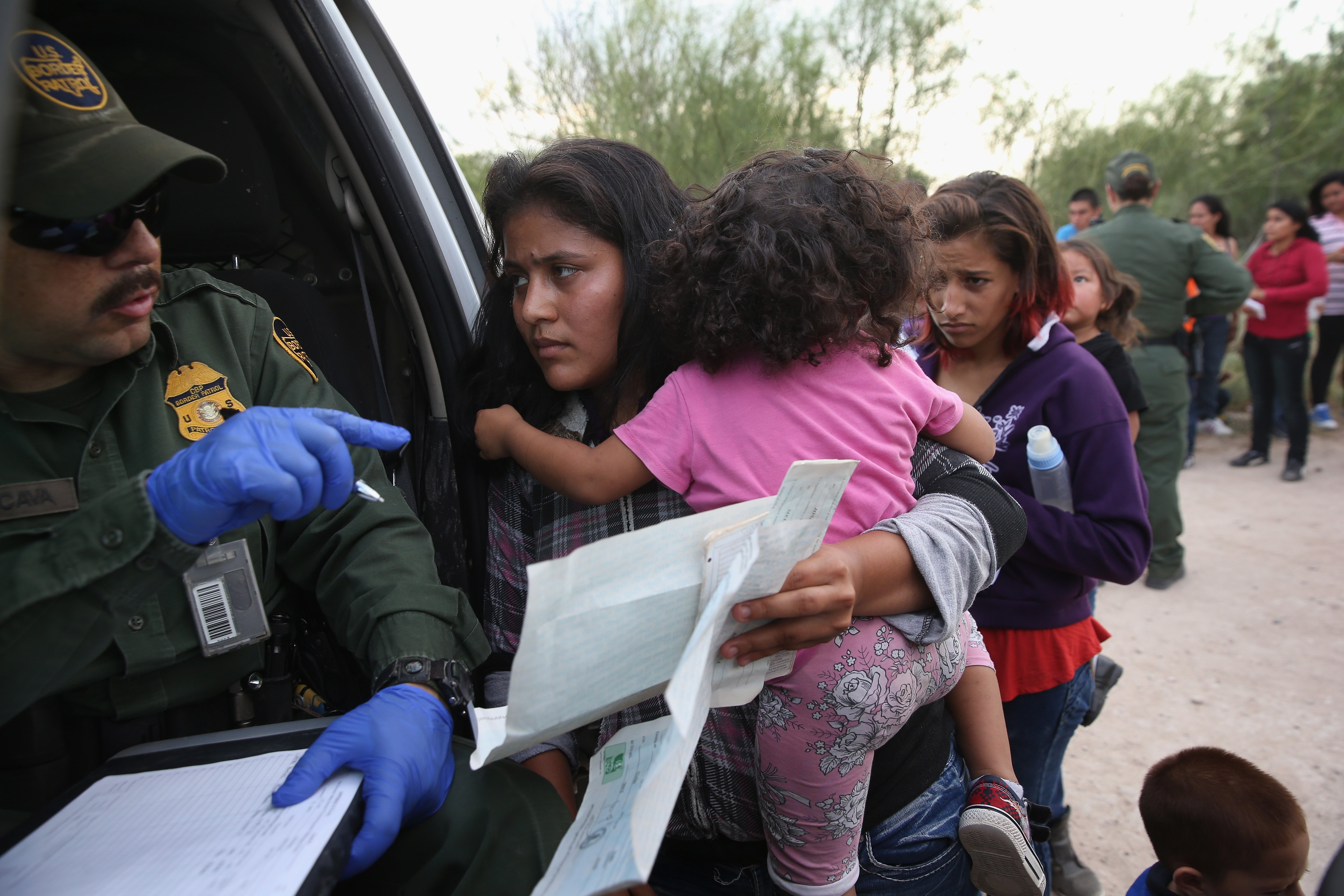Immigrant Melida Patricio Castro from Honduras shows a birth certificate for her daughter Maria Celeste, 2, to a U.S. Border Patrol agent near the U.S.-Mexico border near Mission, Texas on July 24, 2014.