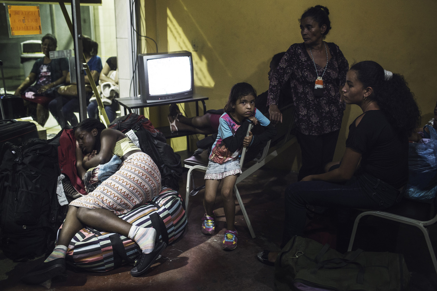 Women and children wait at a bus terminal in San Pedro Sula to begin their journey to the U.S. border