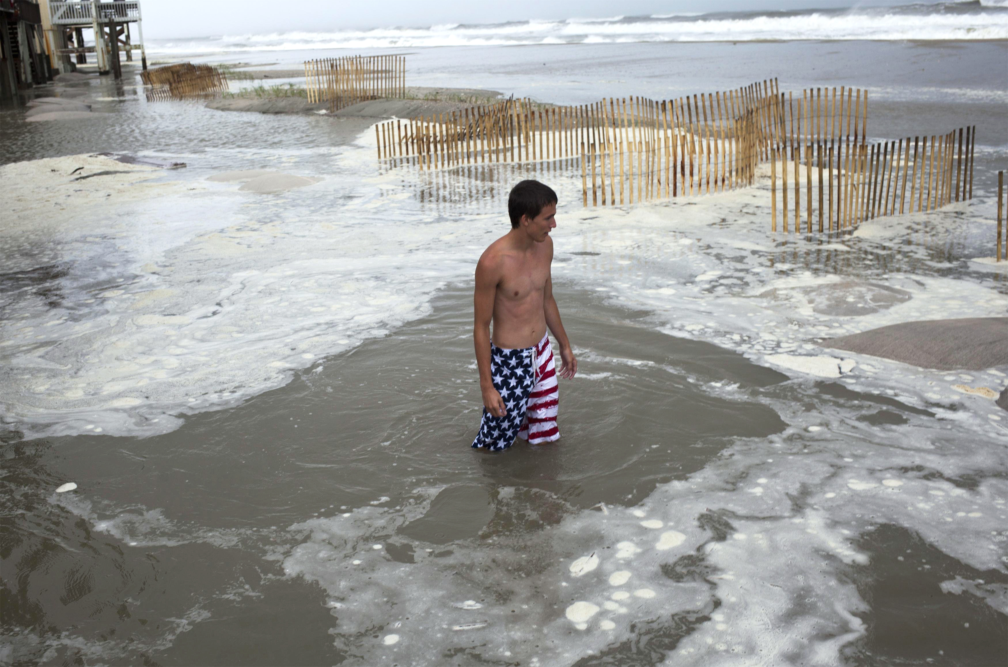 Kyler Cook, 18, walks through the storm surge of Hurricane Arthur in Ocean Isle Beach, N.C., on July 3, 2014.
