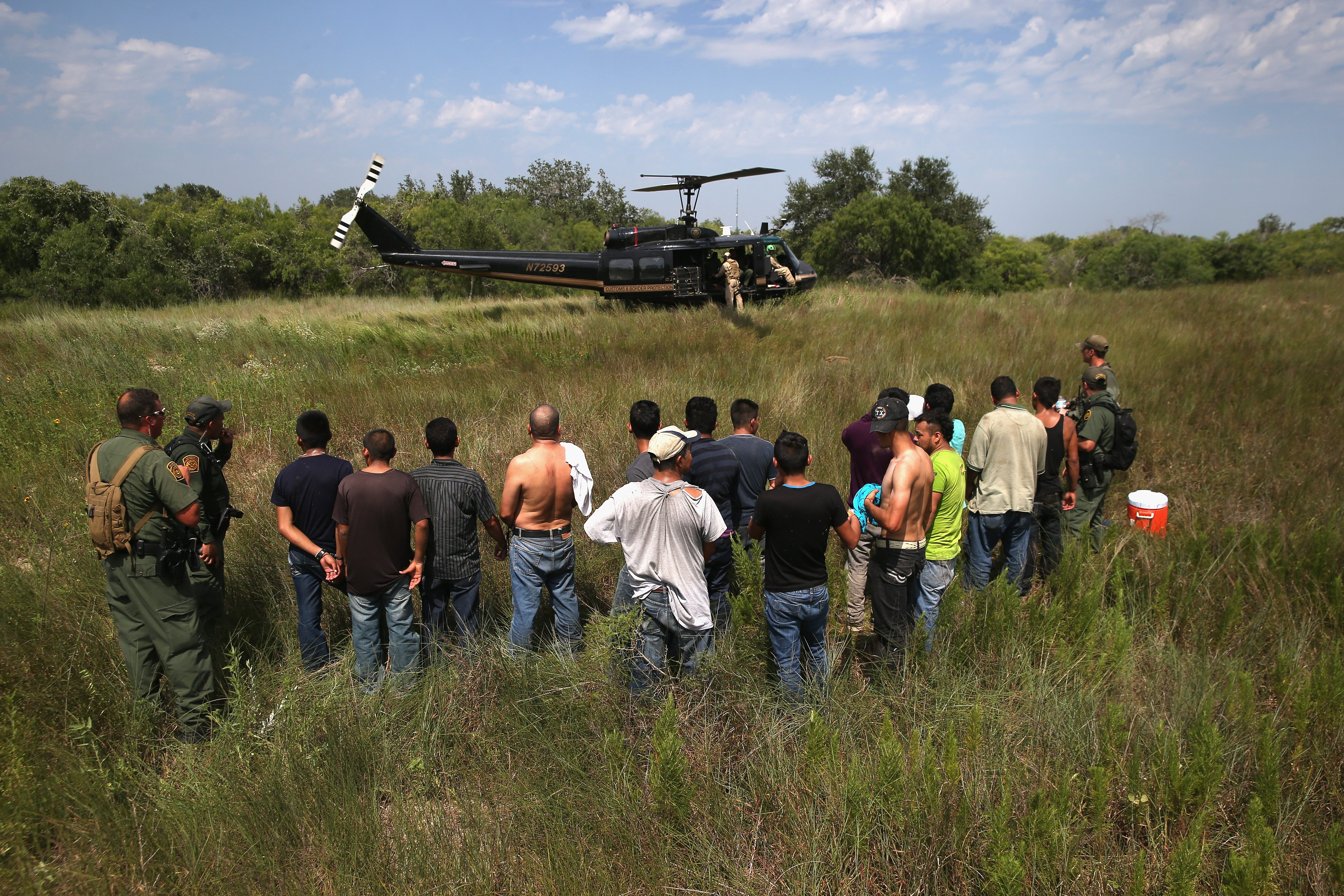 U.S. Border Patrol agents guard undocumented immigrants before sending them to a processing center near Falfurrias, Texas on July 22, 2014.