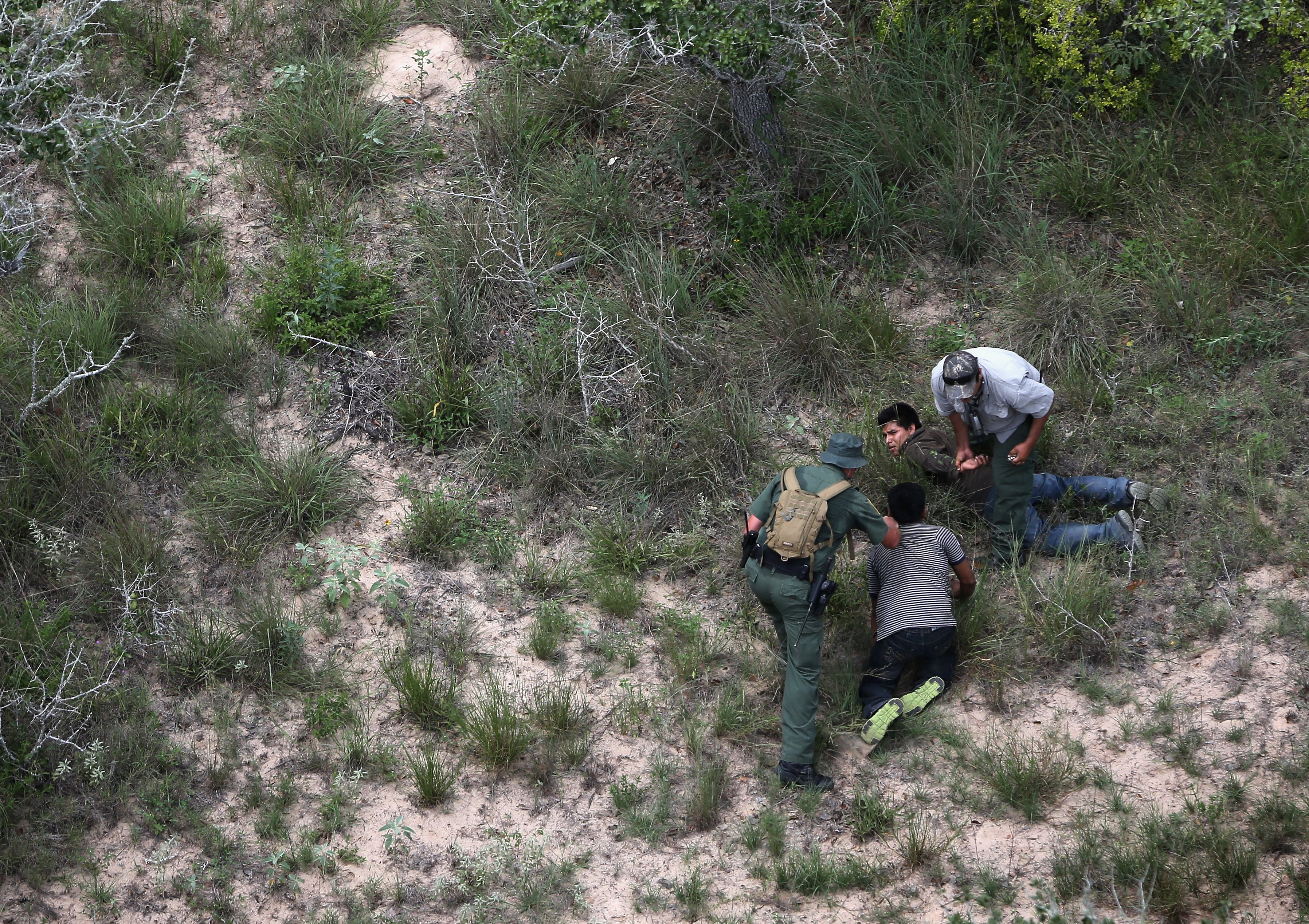 U.S. Border Patrol agents detain undocumented immigrants some 60 miles north of the U.S.-Mexico border near Falfurrias, Texas on July 23, 2014.