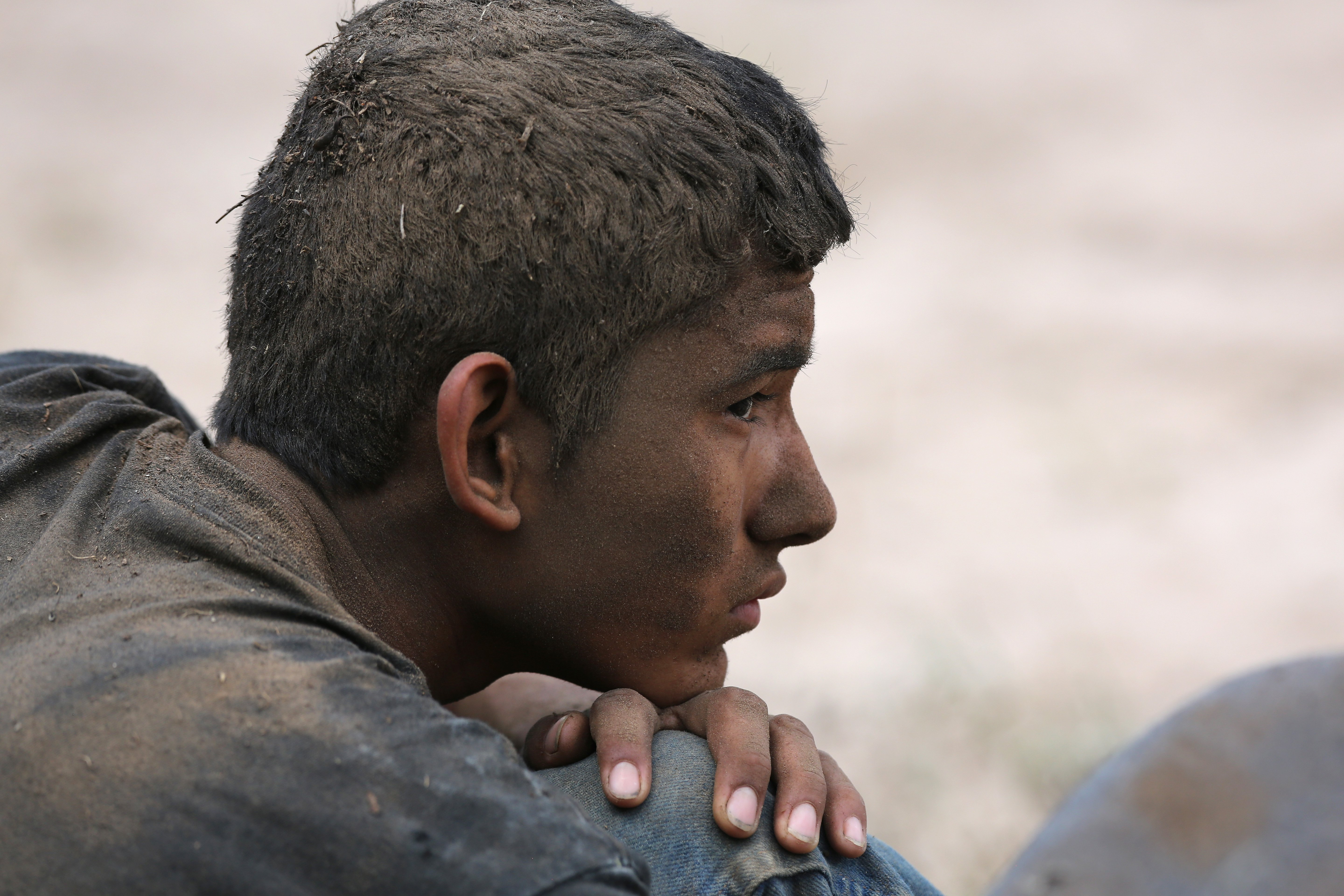 An undocumented immigrant awaits transportation to a processing center after being detained by U.S. Border Patrol agents some 60 miles north of the U.S. Mexico border near Falfurrias, Texas on July 23, 2014.