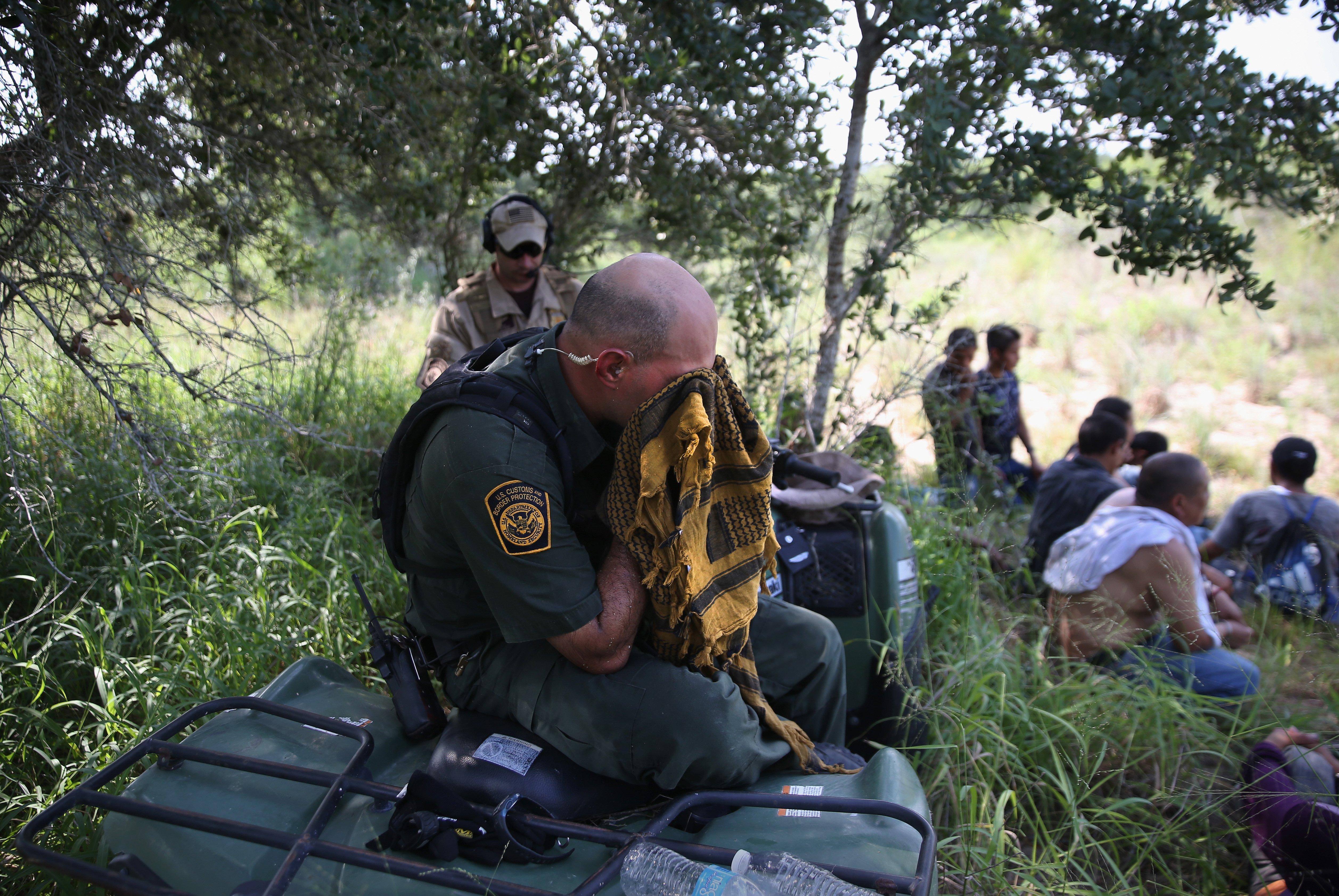 A U.S. Border Patrol agent endures the heat after taking undocumented immigrants into custody near Falfurrias, Texas on July 22, 2014.