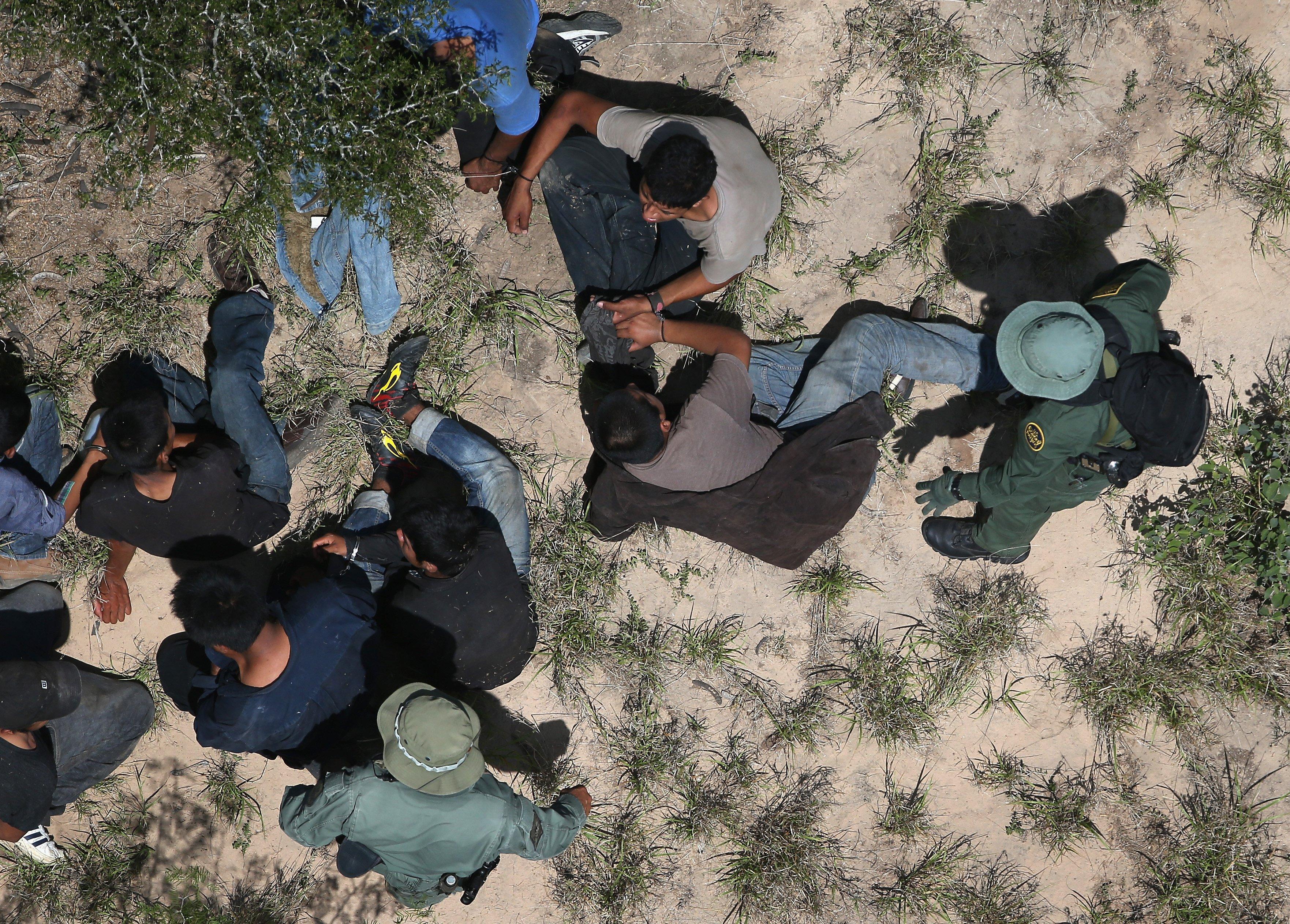 U.S. Border Patrol agents take undocumented immigrants into custody near Falfurrias, Texas on July 21, 2014.