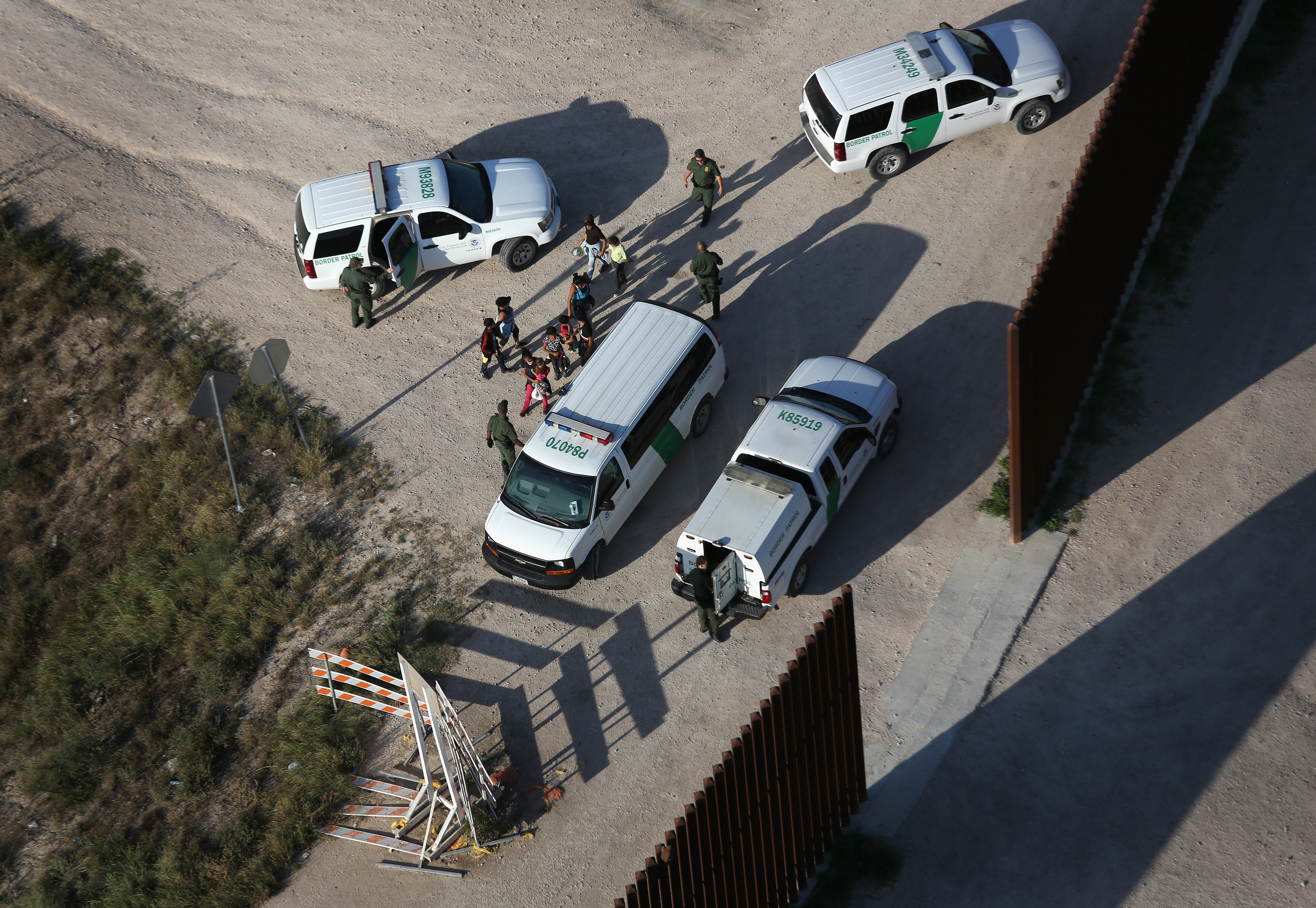 U.S. Border Patrol agents take undocumented immigrant families into custody at the border fence in McAllen, Texas on July 21, 2014.