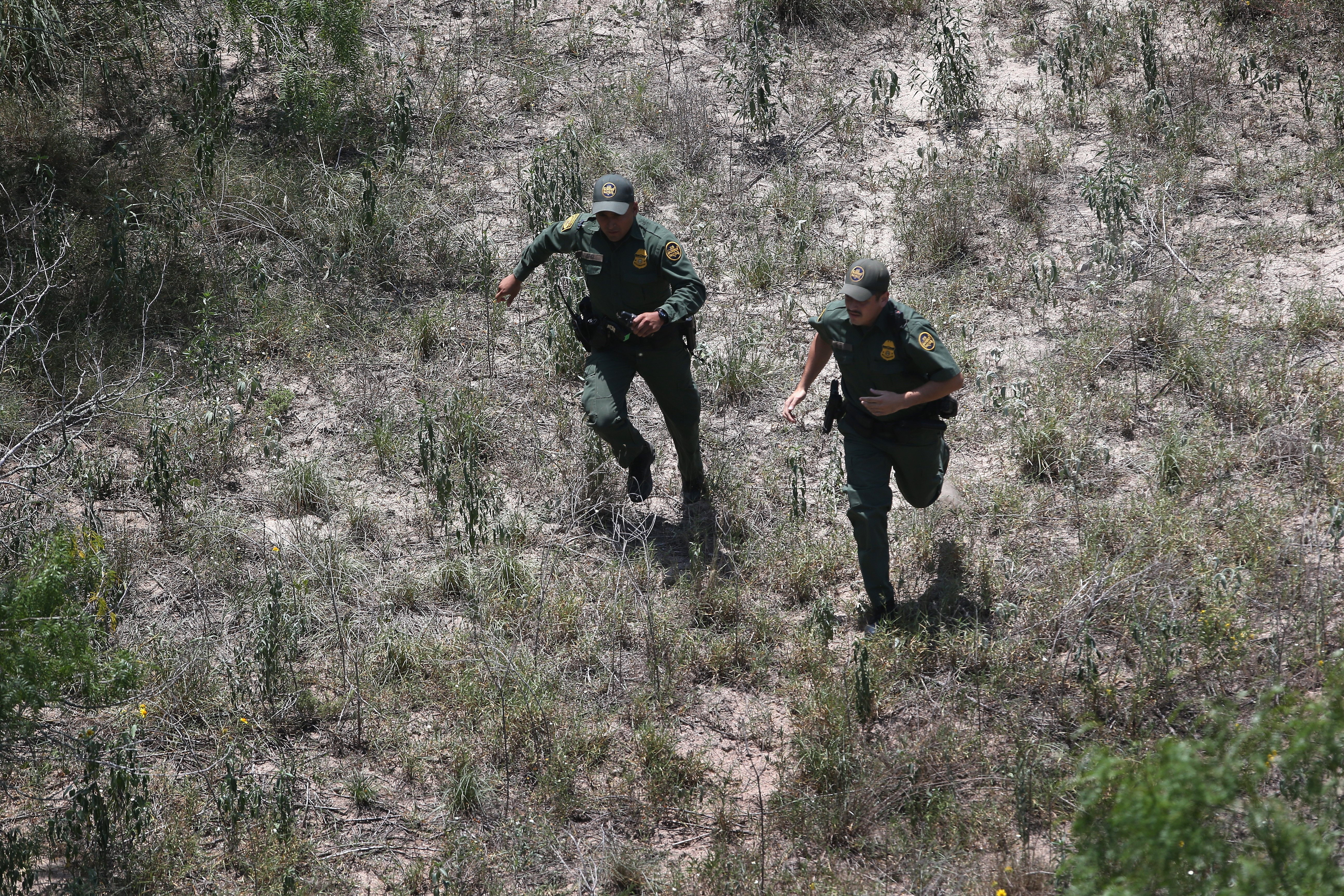 U.S. Border Patrol agents chase undocumented immigrants through the countryside near Falfurrias, Texas on July 22, 2014.
