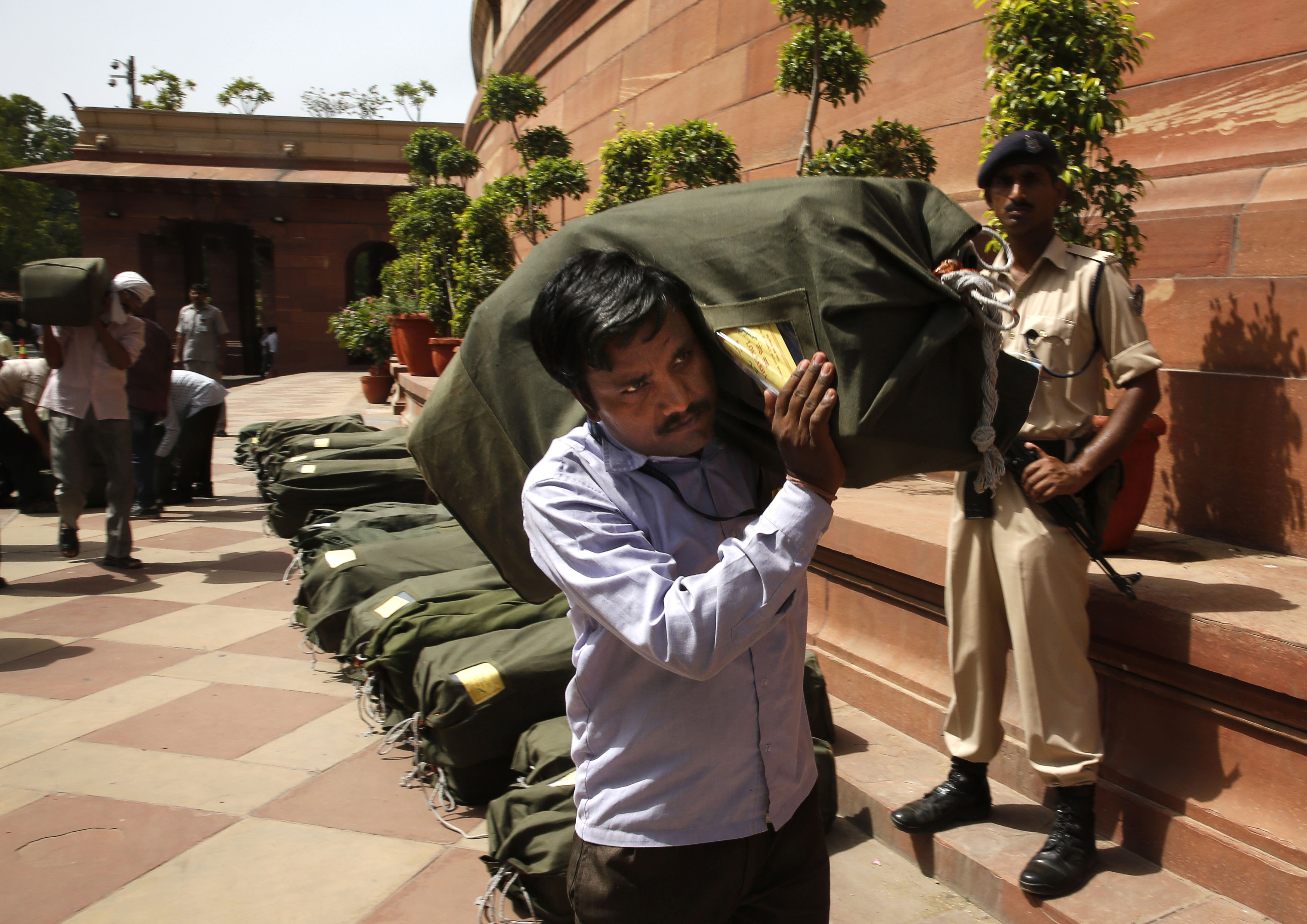 An Indian worker carries a sack containing copies of the 2014-15 union budget at the Indian parliament in New Delhi, Thursday, July 10, 2014.