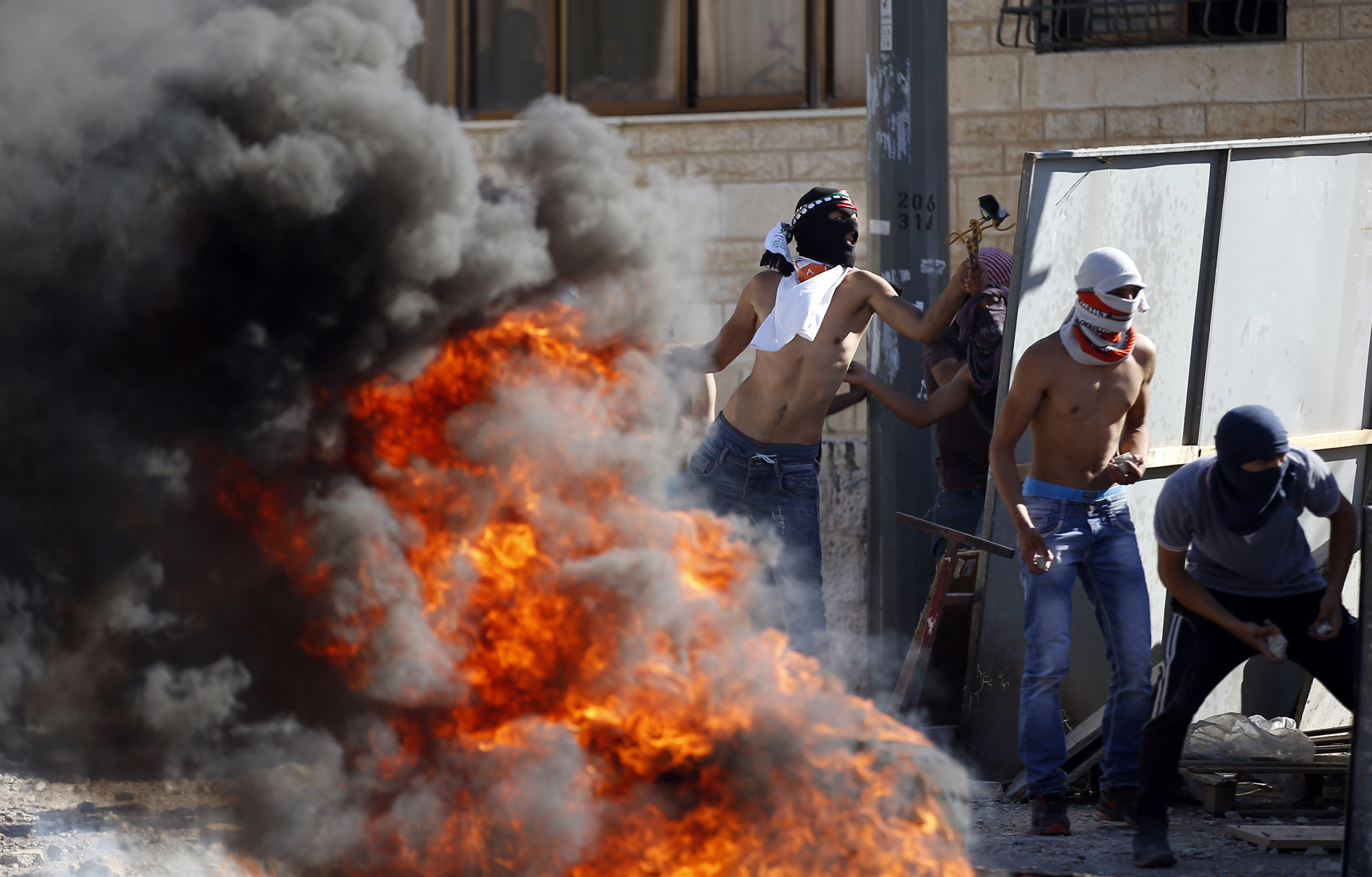 Masked Palestinian protesters throw stones towards Israeli police during clashes in the Shuafat suburb of Jerusalem, on July 2.