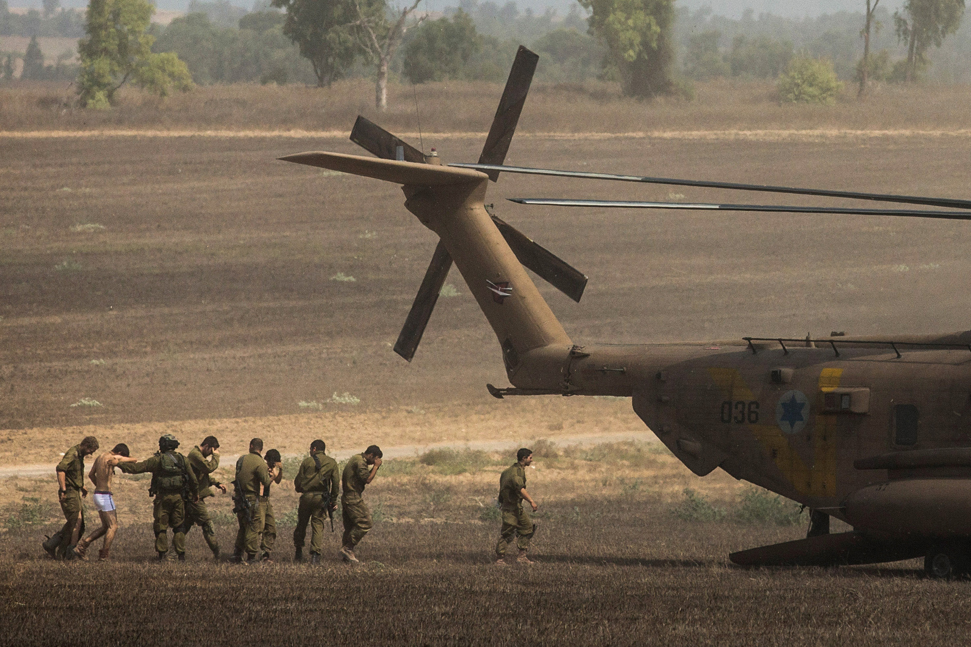 Wounded Israeli soldiers are brought to a helicopter on July 23, 2014 near Kafar Aza, Israel.