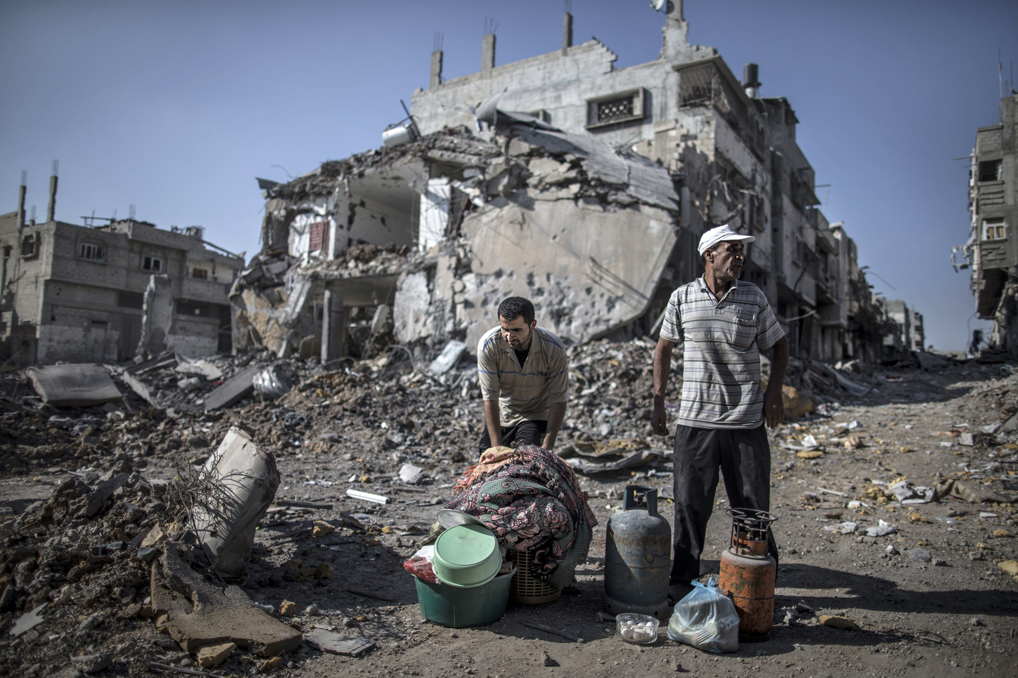 Palestinian men gather things they found in the rubble of destroyed buildings on July 27, 2014 in the Shejaiya residential district of Gaza City as families returned to find their homes ground into rubble by relentless Israeli tank fire and air strikes.