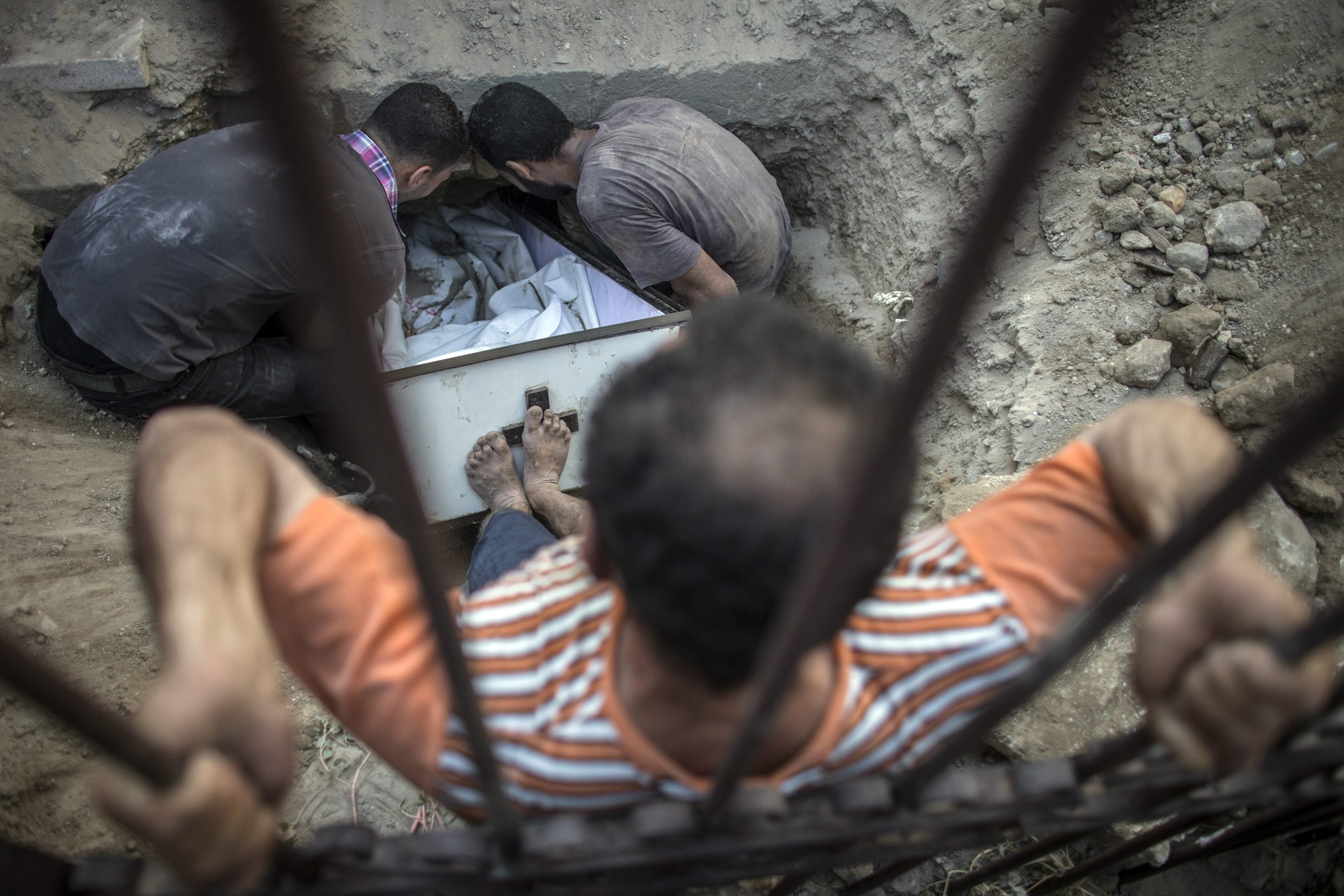 A Palestinian Christian man from Gaza tries to push the coffin of Jalila Ayad in her grave during her funeral on the small and overcrowded cemetery of the St. Porfirius church in Gaza City, July 27, 2014.