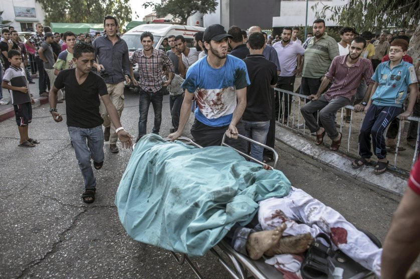 Palestinian men rush the bodies of two dead children from the emergency room to the morgue of Shifa hospital in Gaza City, July 28, 2014.