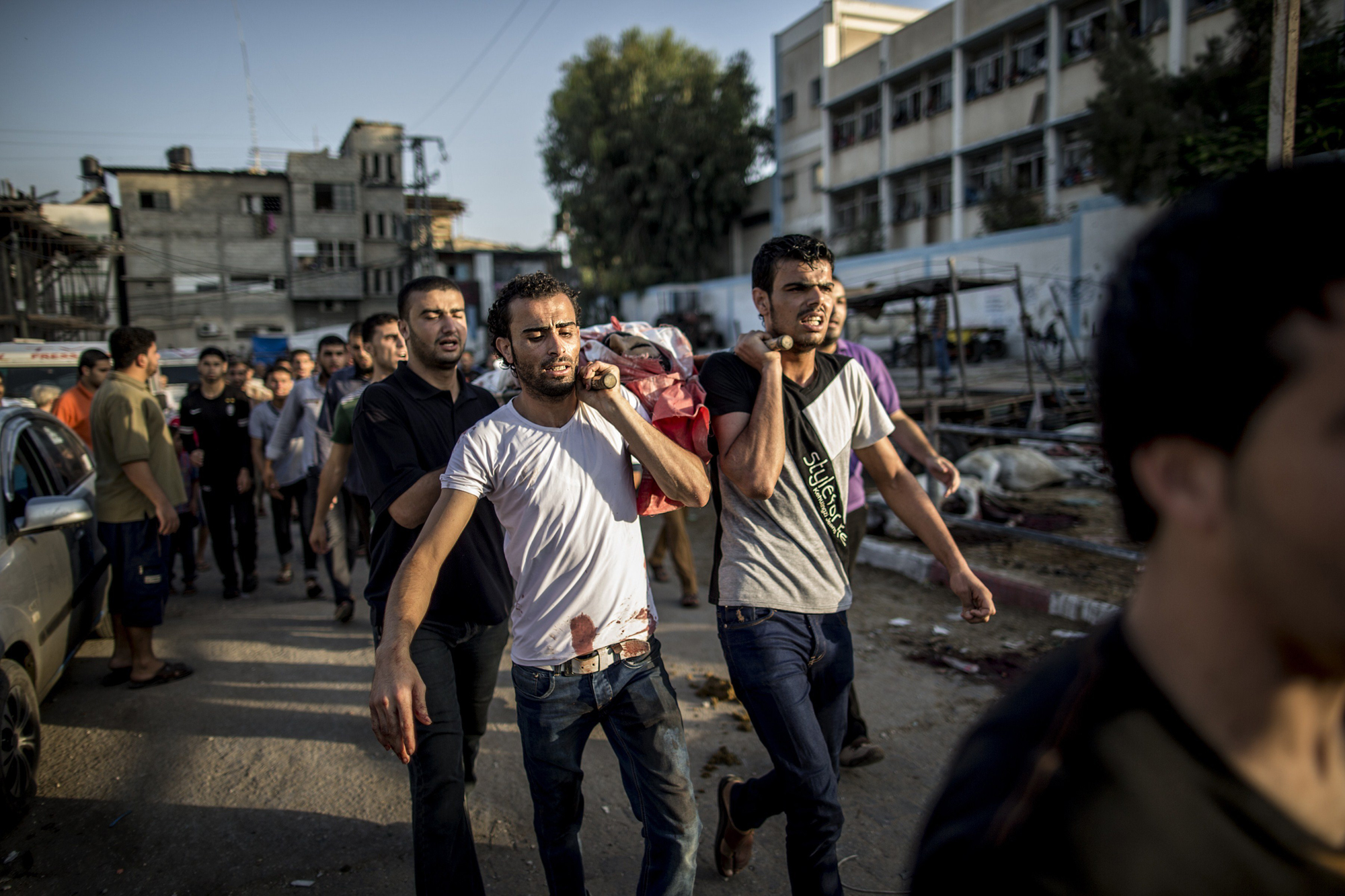 Palestinian mourners carry a body as they walk during a funeral procession past a UN school that was hit by Israeli shelling in the Jabalia refugee camp on July 30, 2014.