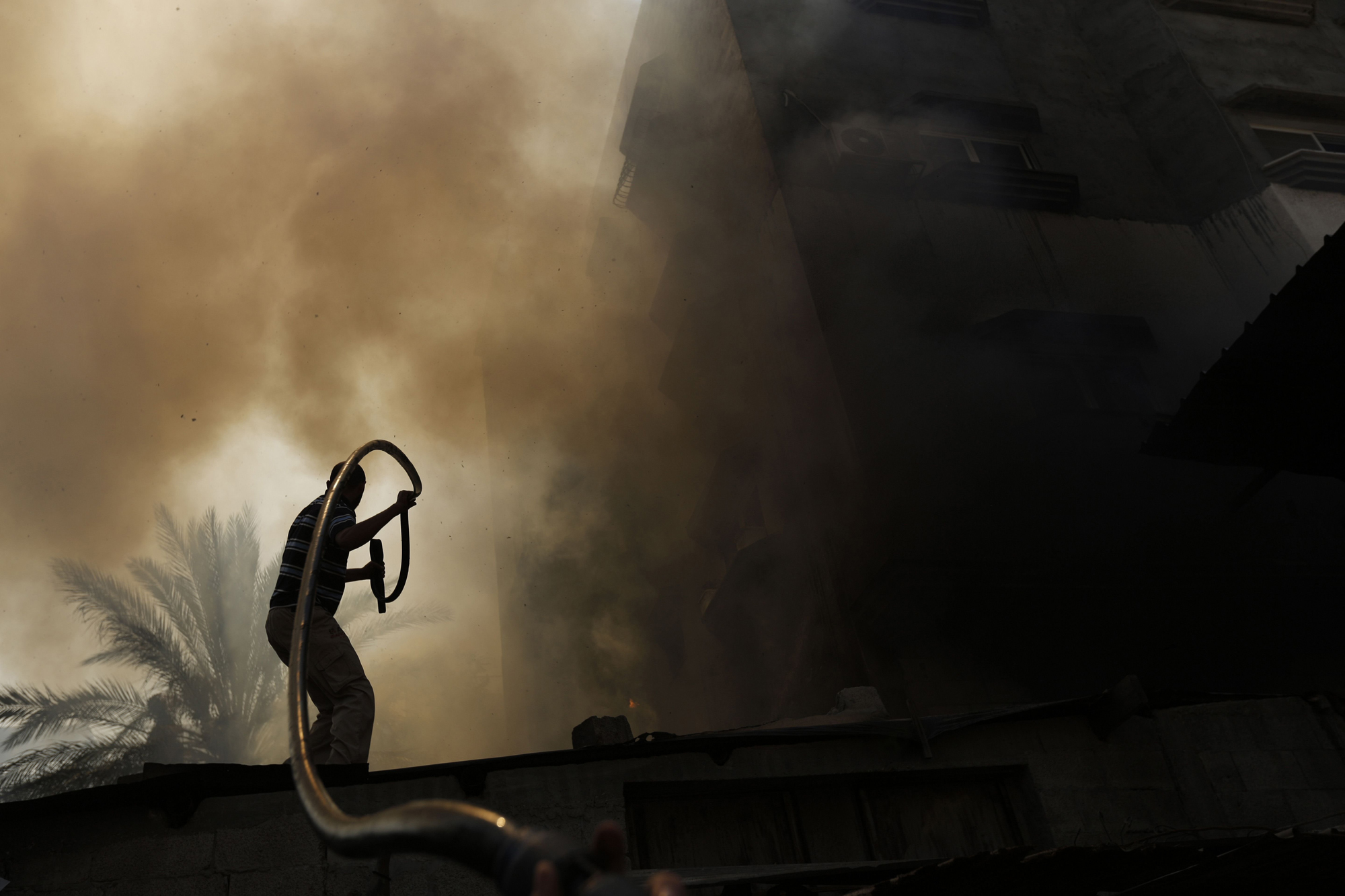A Palestinian man battles a building on fire following several Israeli strikes on Gaza City on July 30, 2014.