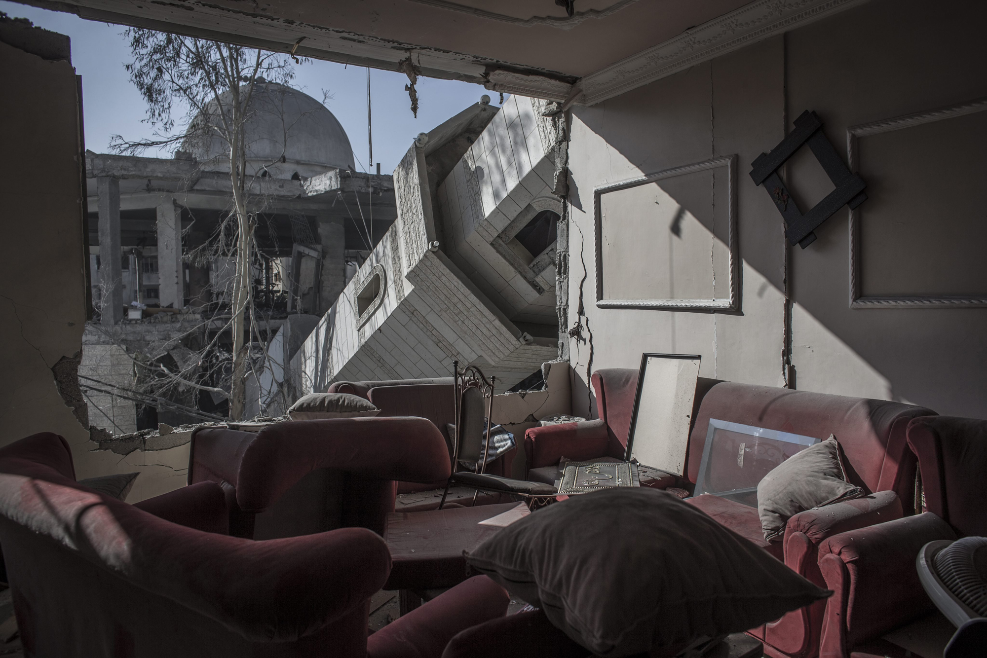 The collapsed minaret of mosque seen from the destroyed living room of a Palestinian family in a building across the street in Gaza City, Gaza Strip, July 30, 2014.