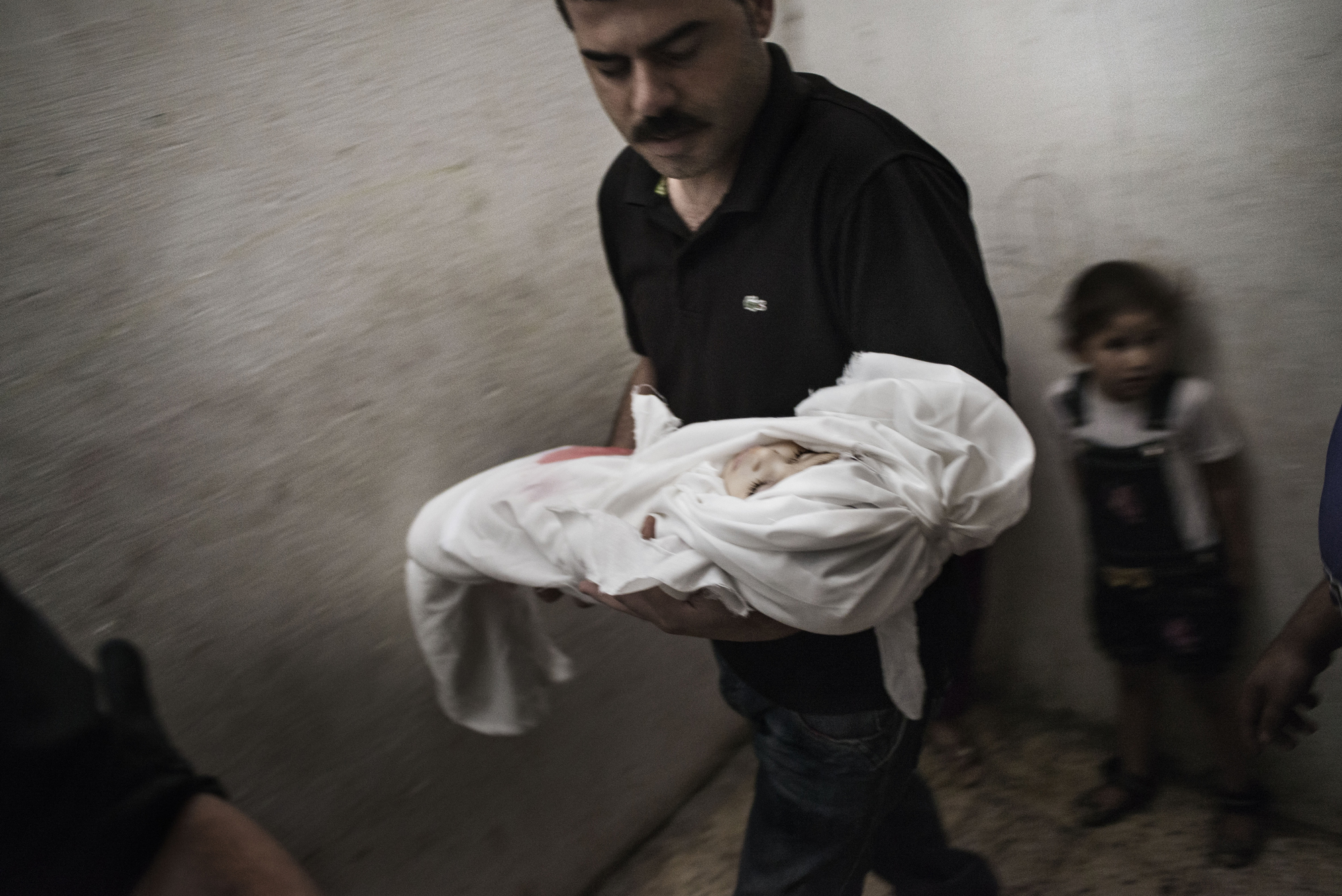 The father of 18-month-old Razel Netzlream, who was fatally wounded during an air strike, carries her body right before her funeral in Rafah, Gaza Strip, on July 18, 2014