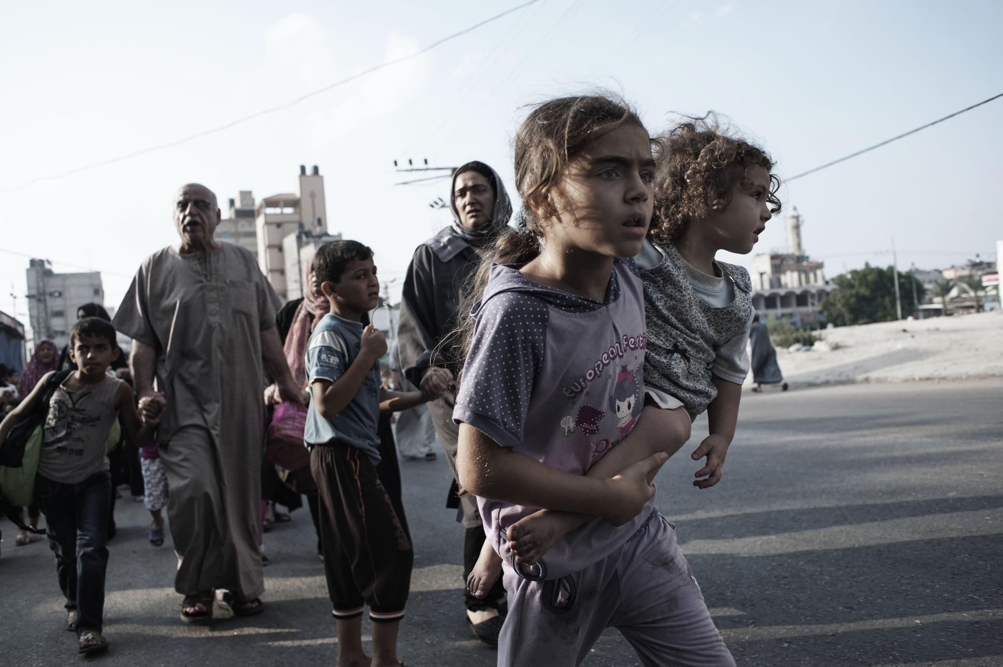 Palestinians flee the Shujayeh neighborhood during heavy shelling in Gaza City, July 20, 2014.