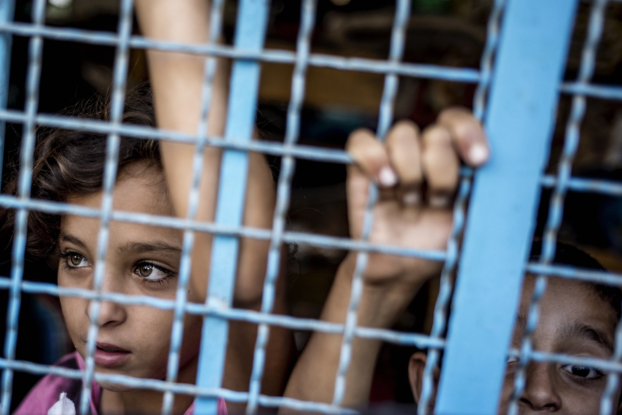 Palestinian girls peers from inside a UN school in Jabalia, north Gaza Strip, on July 25, 2014, where they found shelter after escaping from their home.