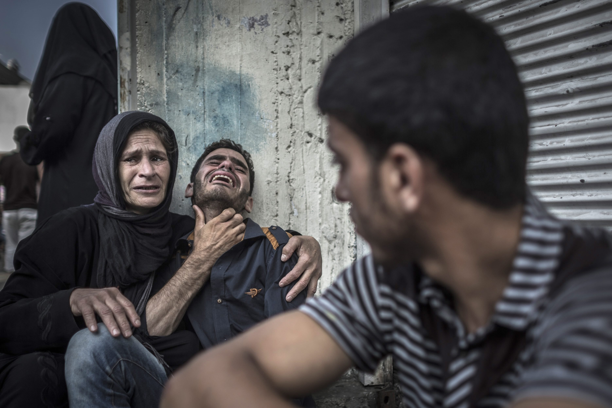 Palestinians mourn the death of a relative, who died when a UN school used as a shelter for internally displace people came under Israeli shelling in the Kamal Adwan hospital in Beit Lahia, northern Gaza Strip, July 30, 2014.