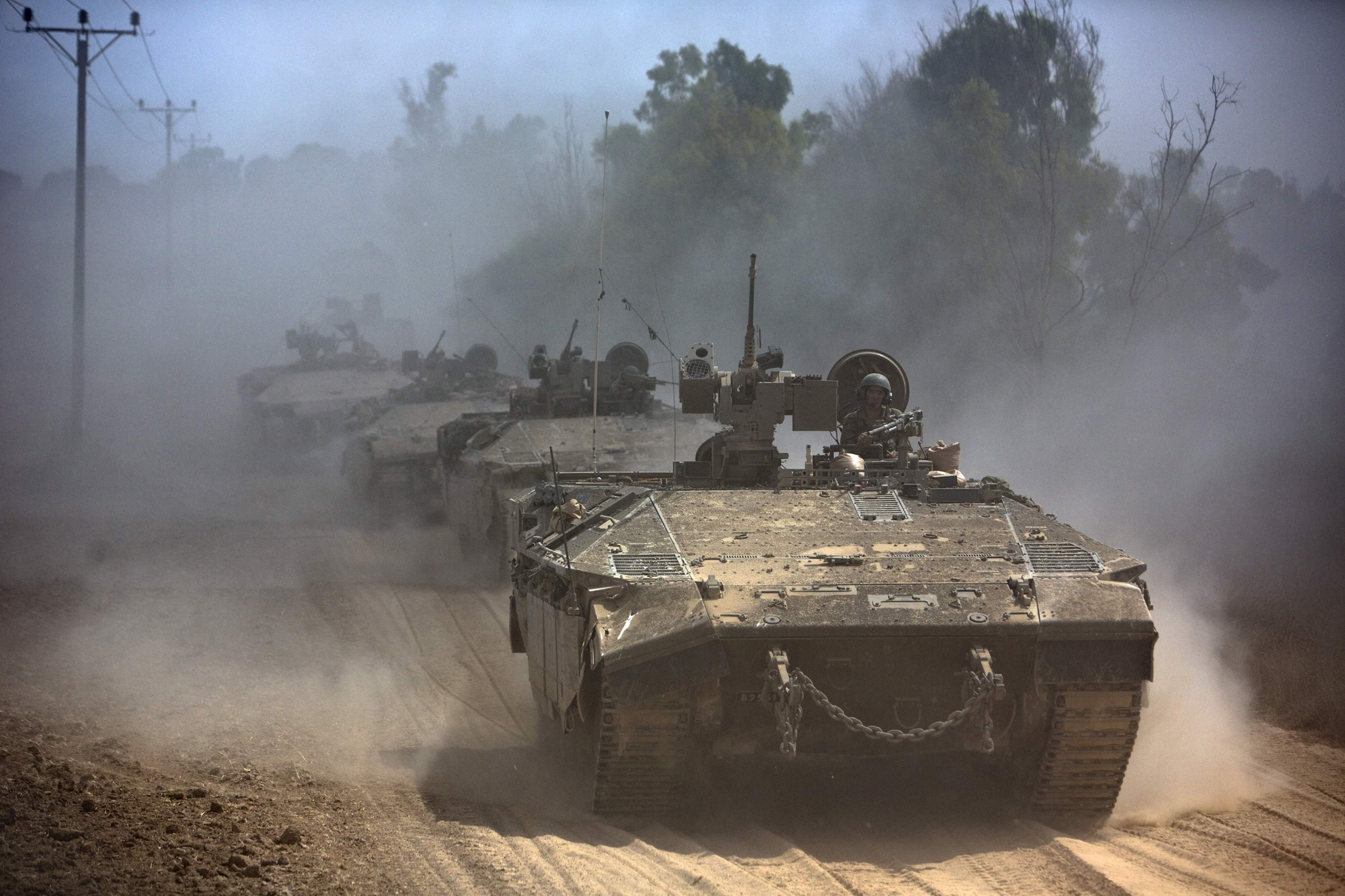 Israeli APCs drive near the Israeli border with Gaza as they come out of the Gaza Strip July 25, 2014.