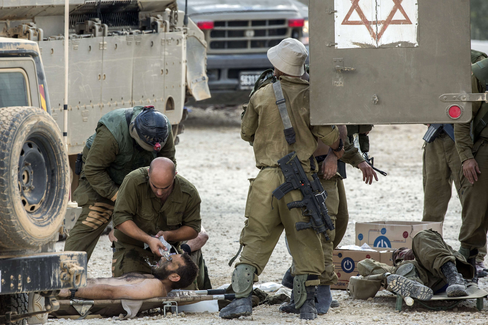 Israeli soldiers evacuate their wounded comrades at an army deployment area near Israel's border with the Gaza Strip, on July 20, 2014.