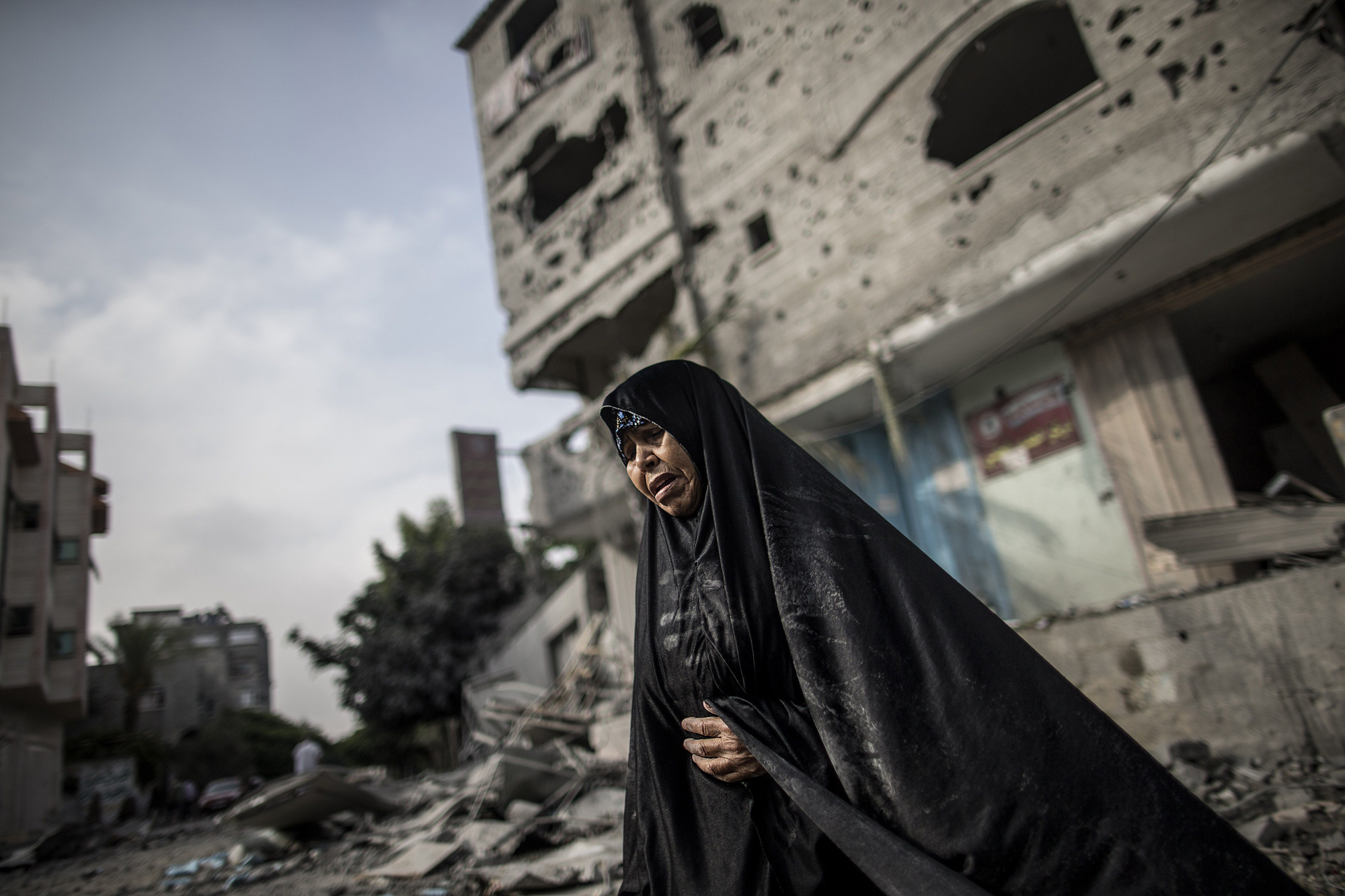 A Palestinian woman stands in front of buildings damaged by Israeli bombardment in the Jabalia district of the northern Gaza Strip on July 24, 2014.