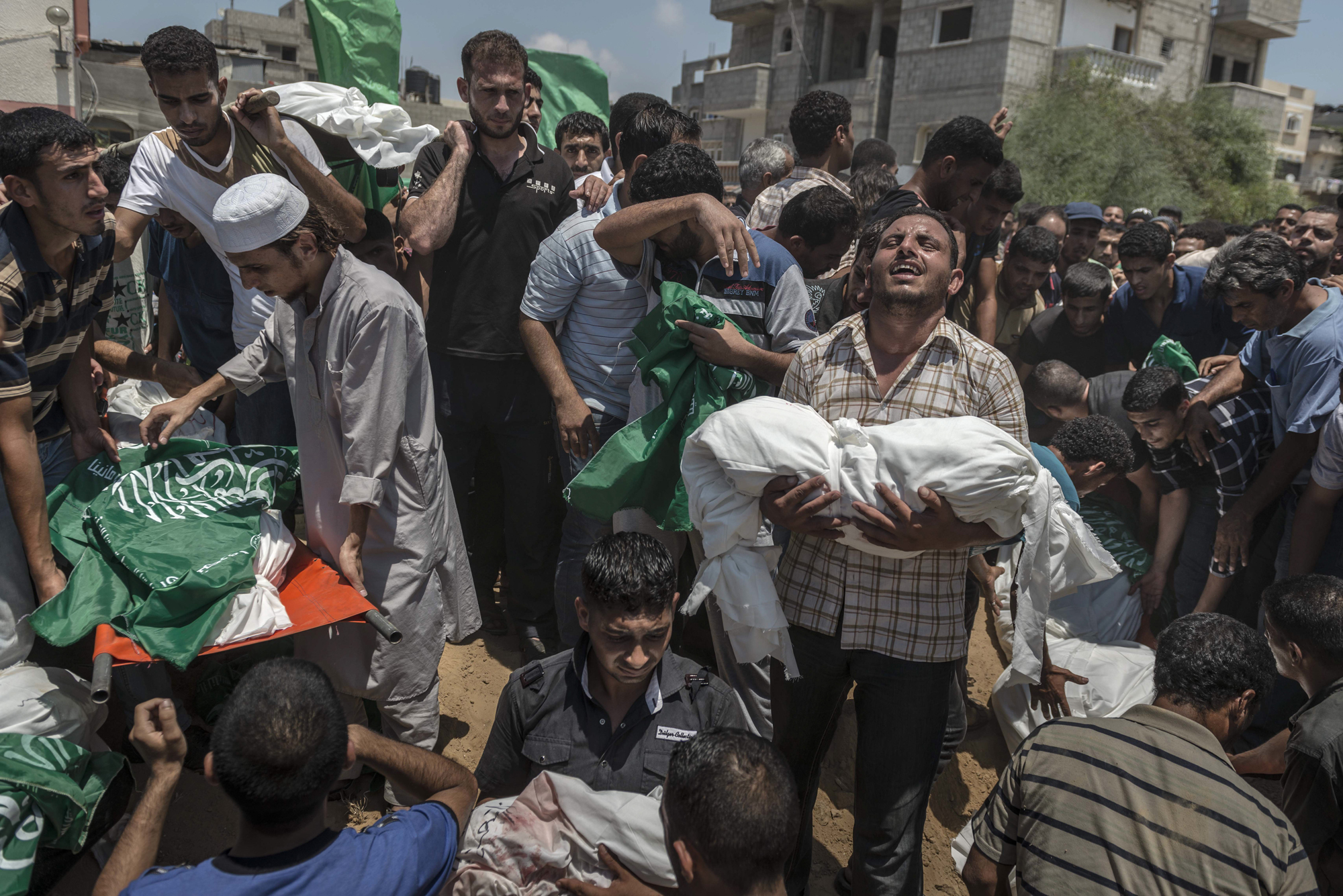 Palestinian men bury the bodies of a family who was killed after airstrike in Khan Younis, in the Gaza Strip, July 21, 2014.