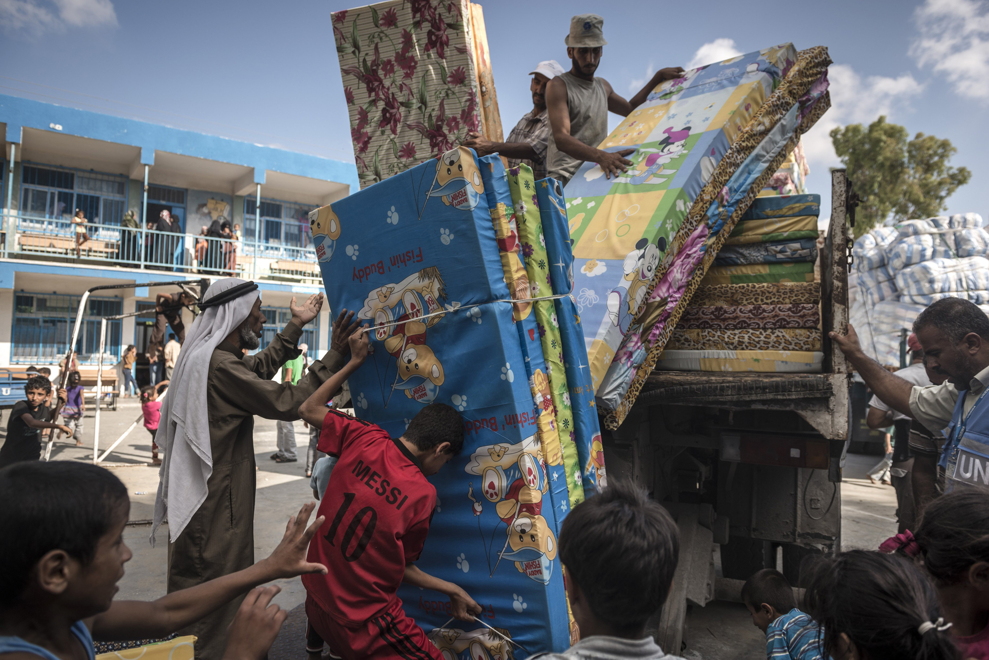 Palestinian refugees unload mattresses at a United Nations shelter in Rafah, Gaza Strip, July 19, 2014.